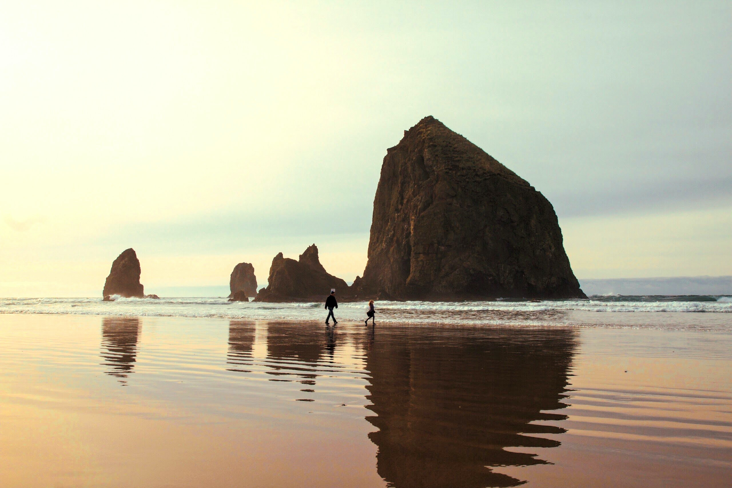People walking along a beach with a rock formation being reflected in the perfectly clear and still water