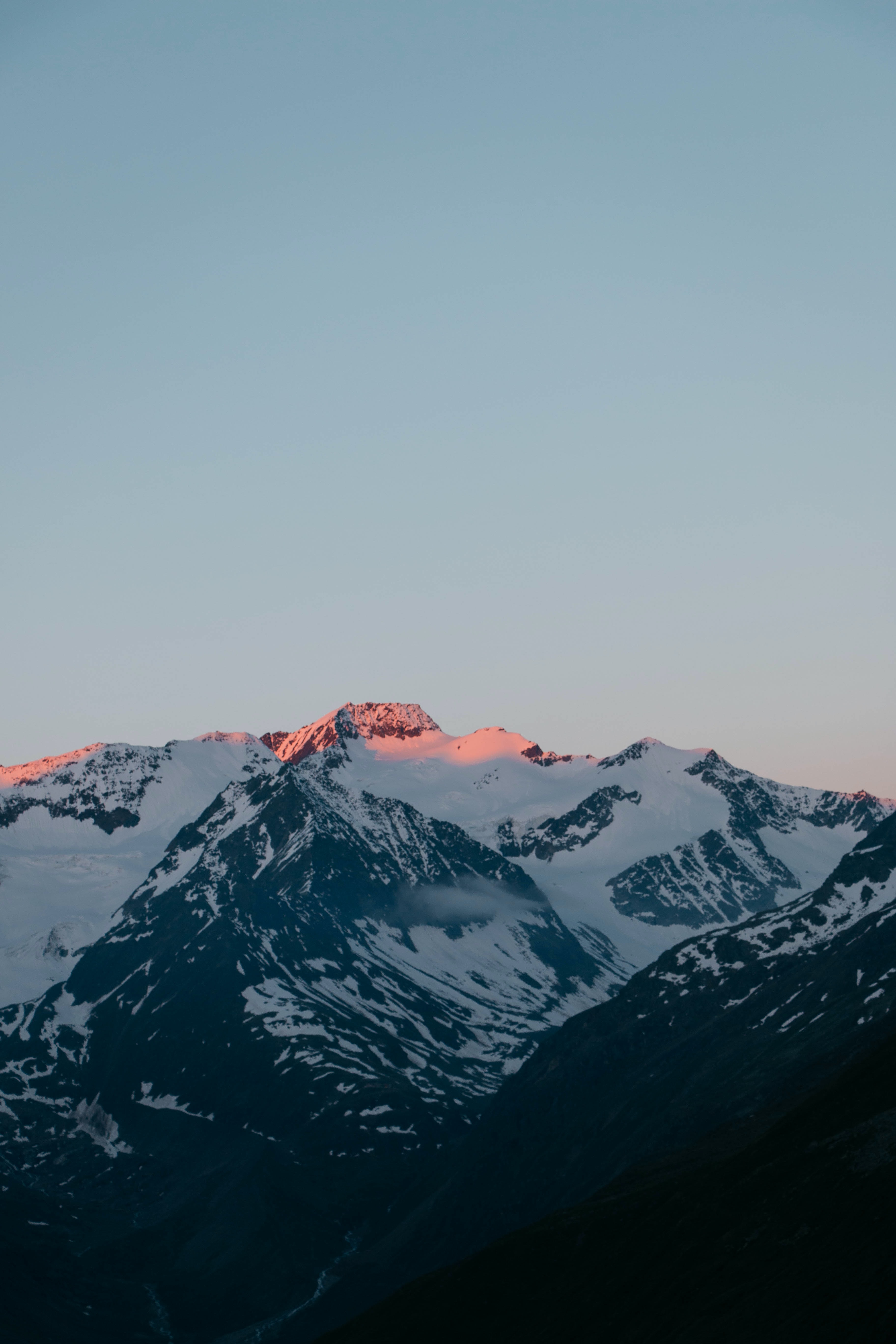 Red light falling on a snowy mountain ridge during sunset