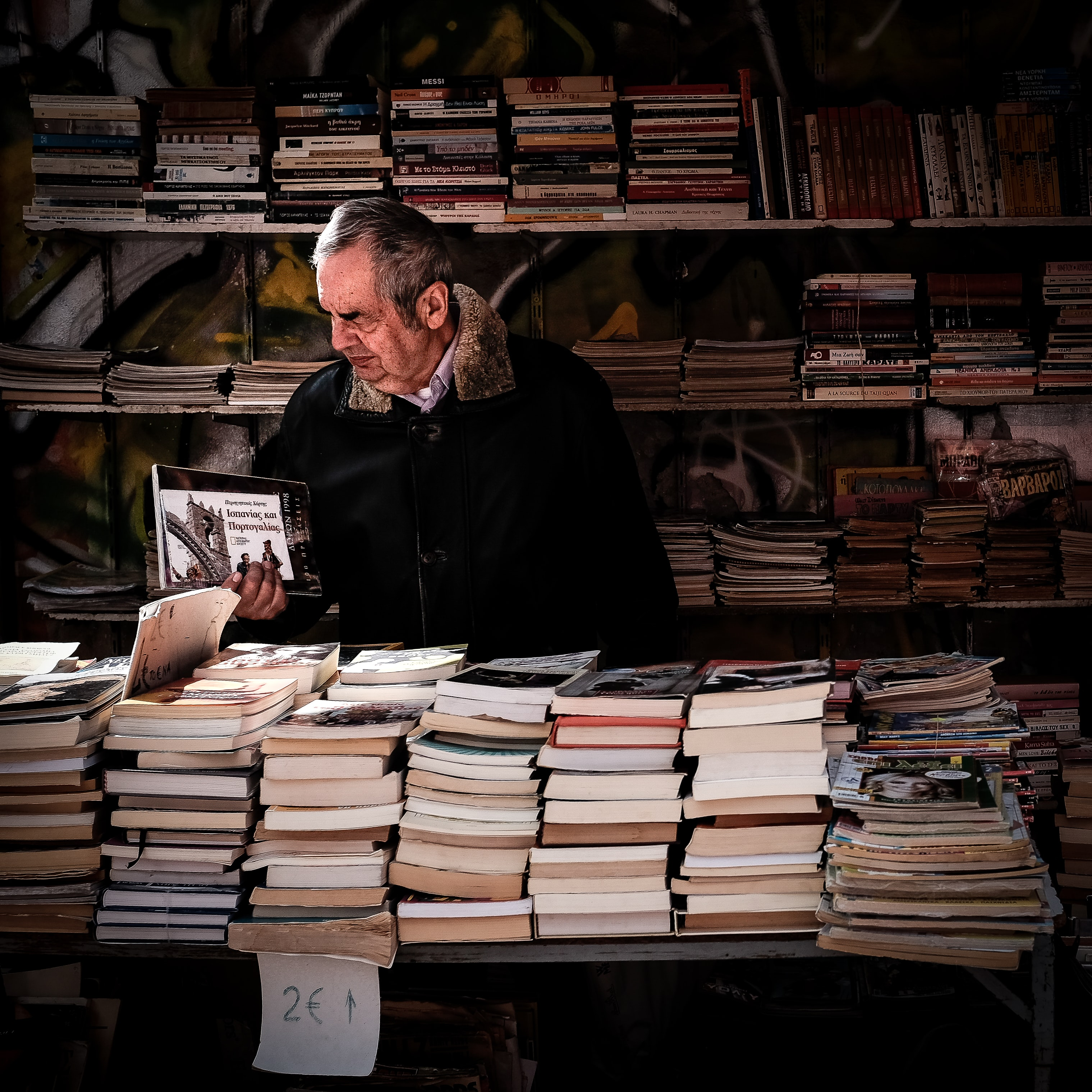 An elderly man browsing books in a bookstore in Athens