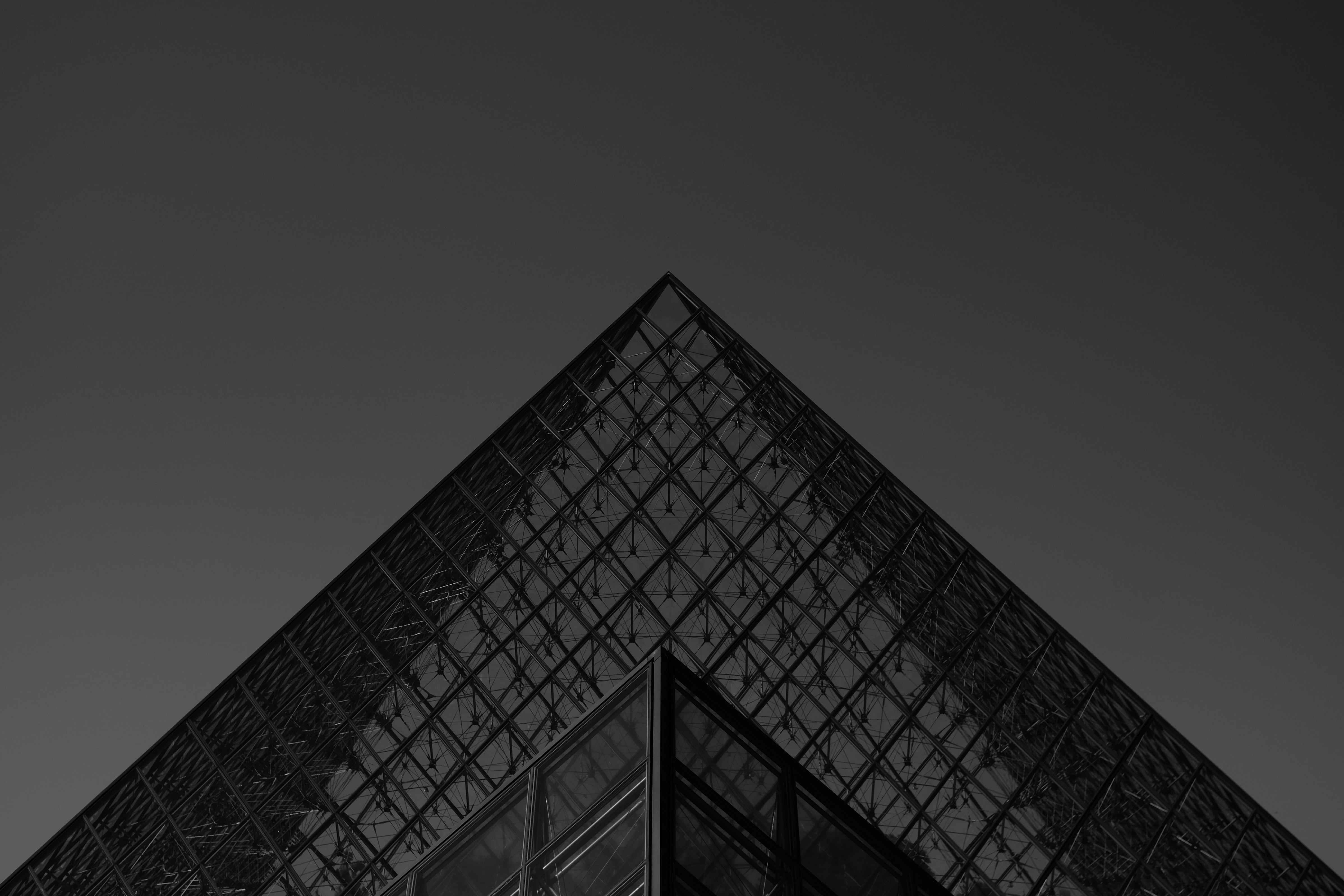 Black and white shot of the glass pyramid at Louvre Museum in Paris