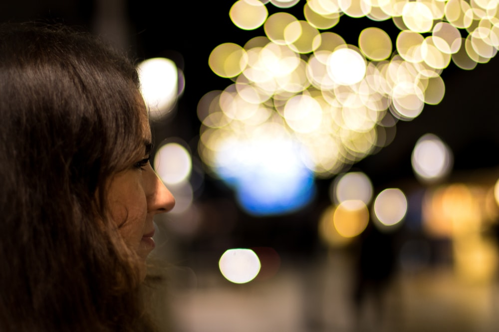 woman facing boke lights