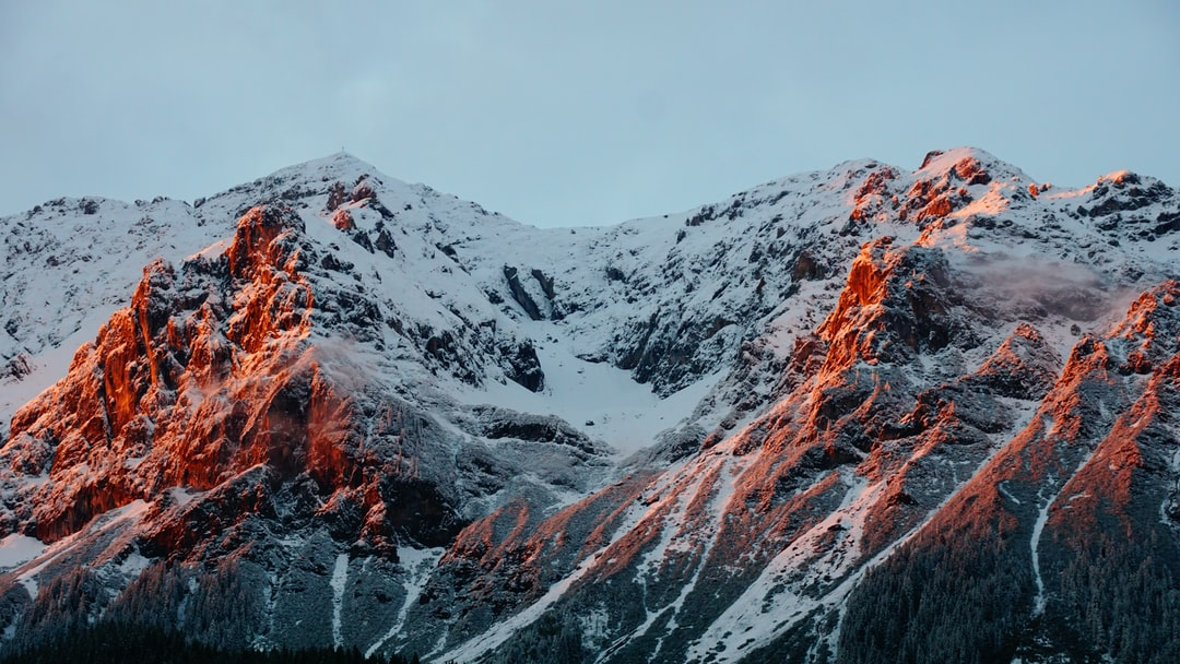 A mountain ridge in the Dachstein Mountains with red sun rays falling on the rocky face