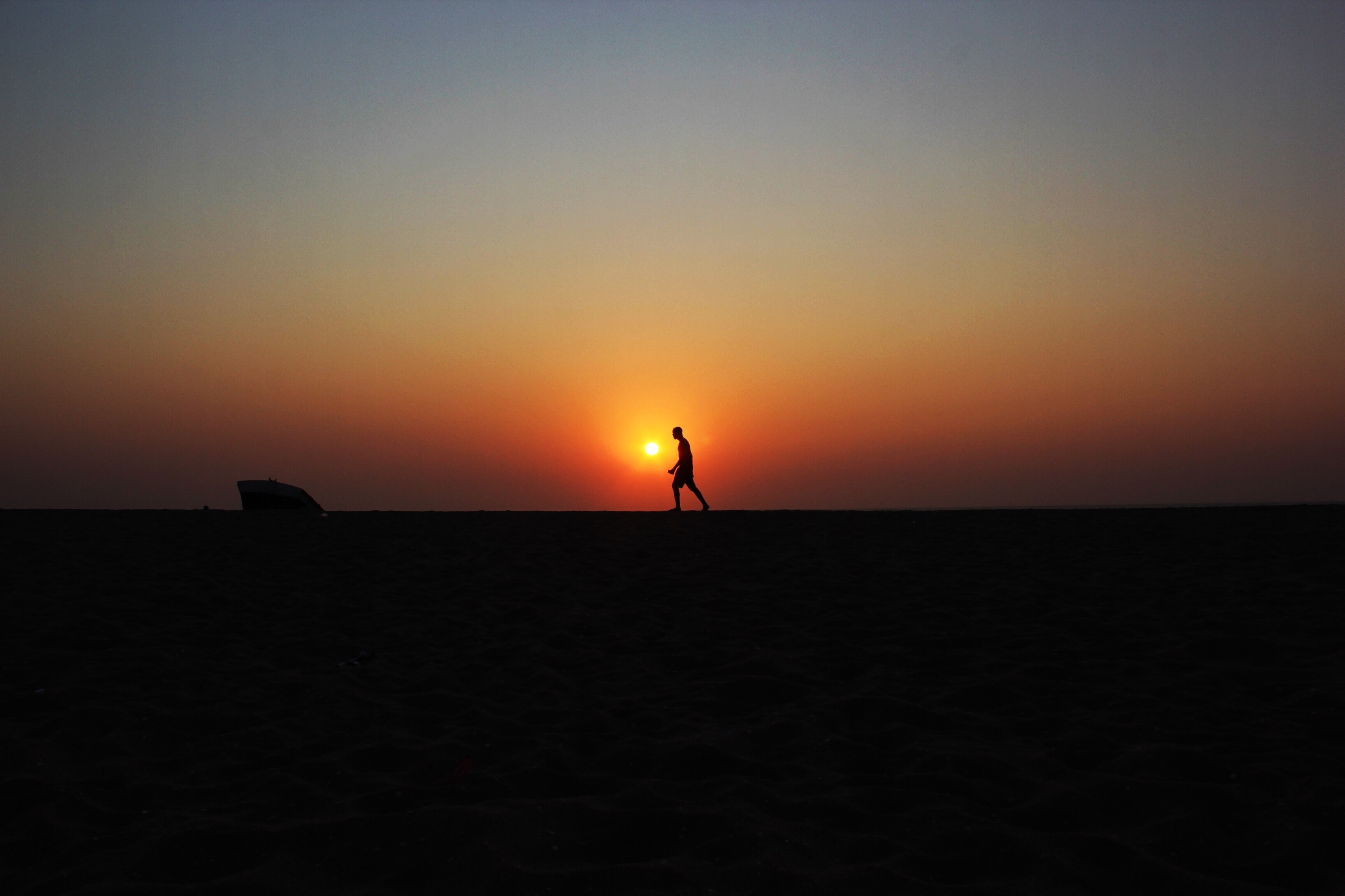 The silhouette of a man walking on the beach during sunset in Luanda