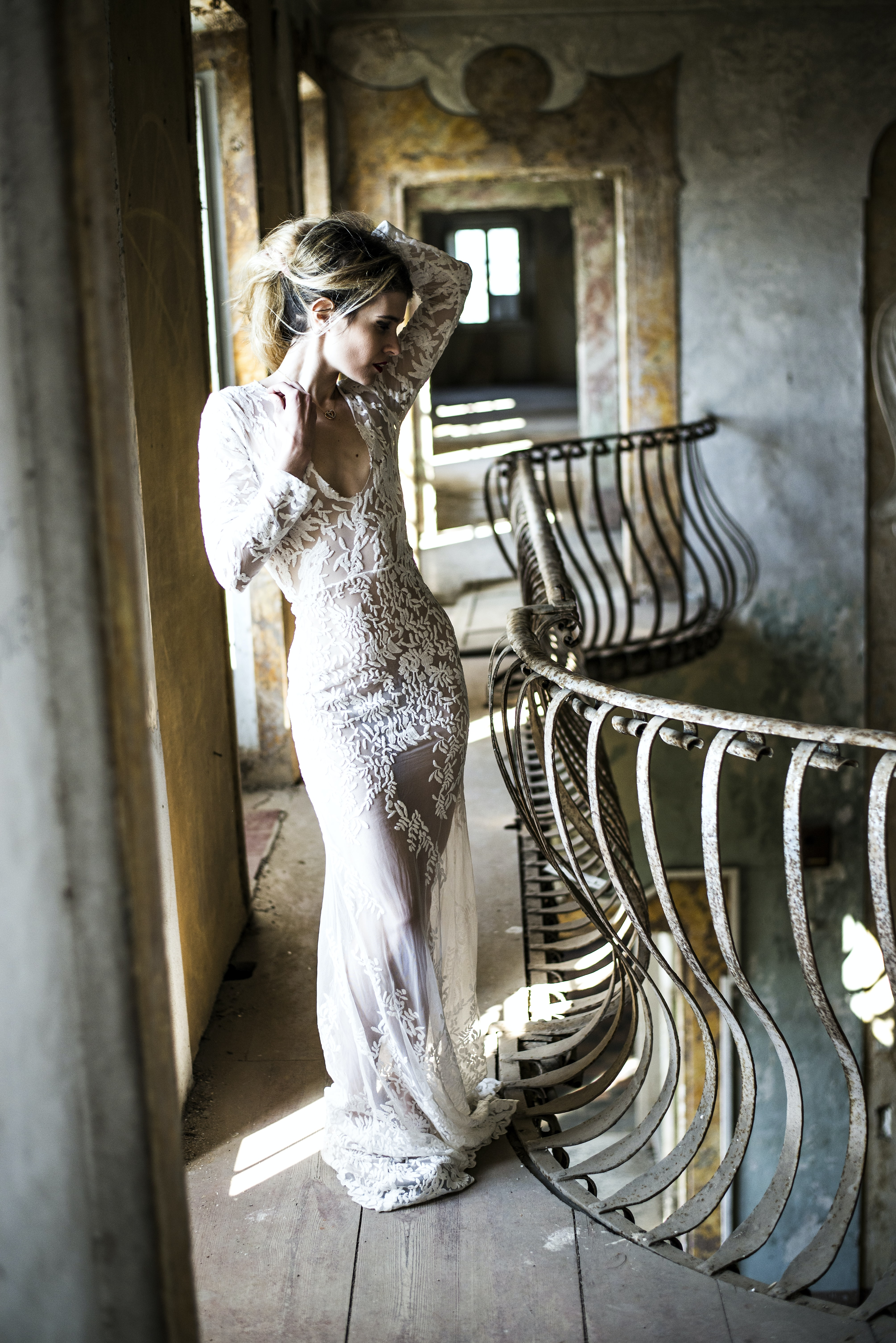 Curvy bride poses with hair up ar curved railing