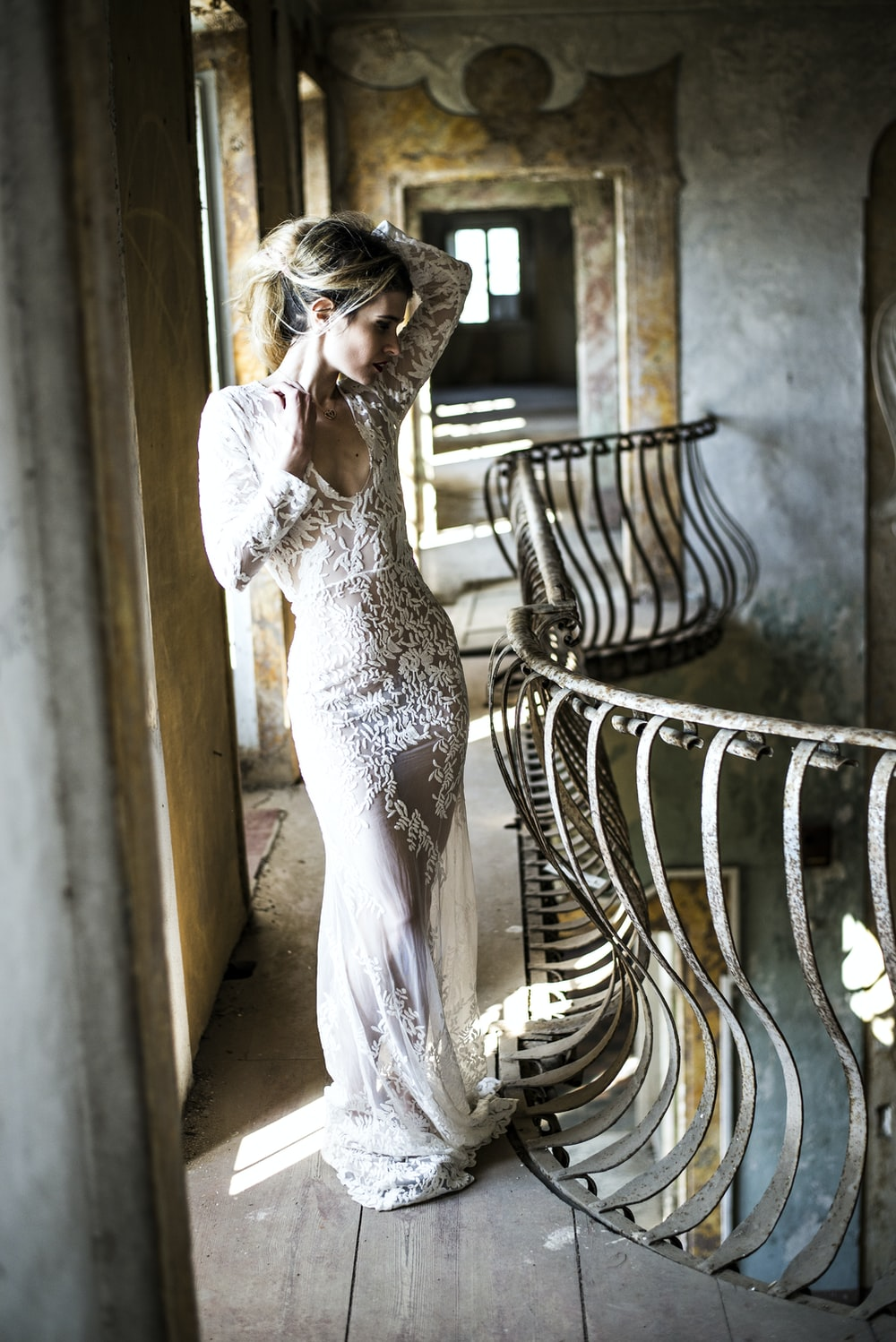 woman in white floral lace scoop-neck long-sleeved dress standing beside rail in concrete building during daytime