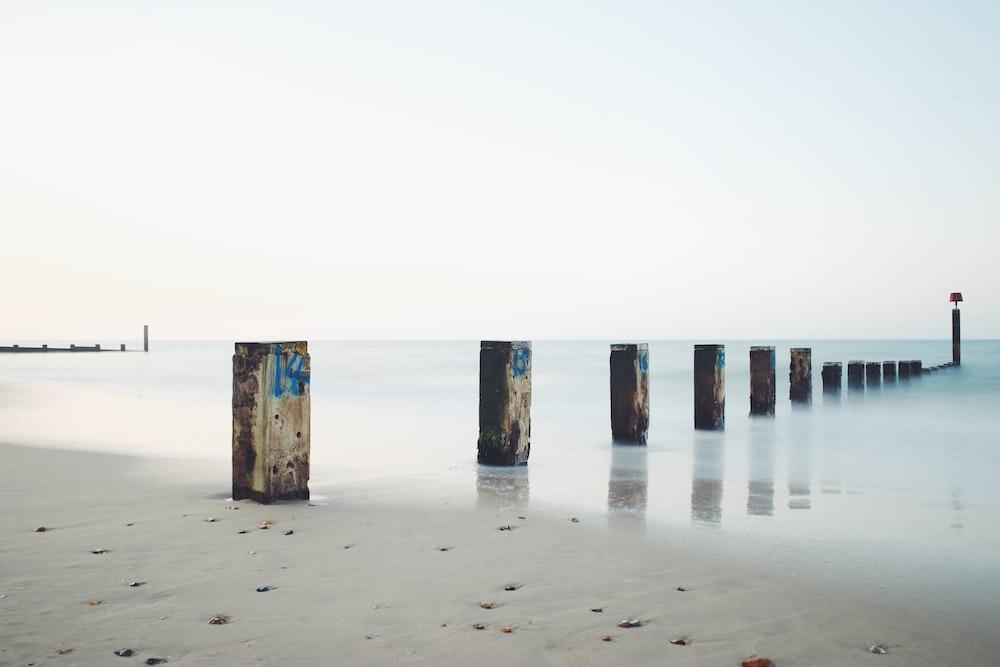 gray concrete post on seashore under gray sky