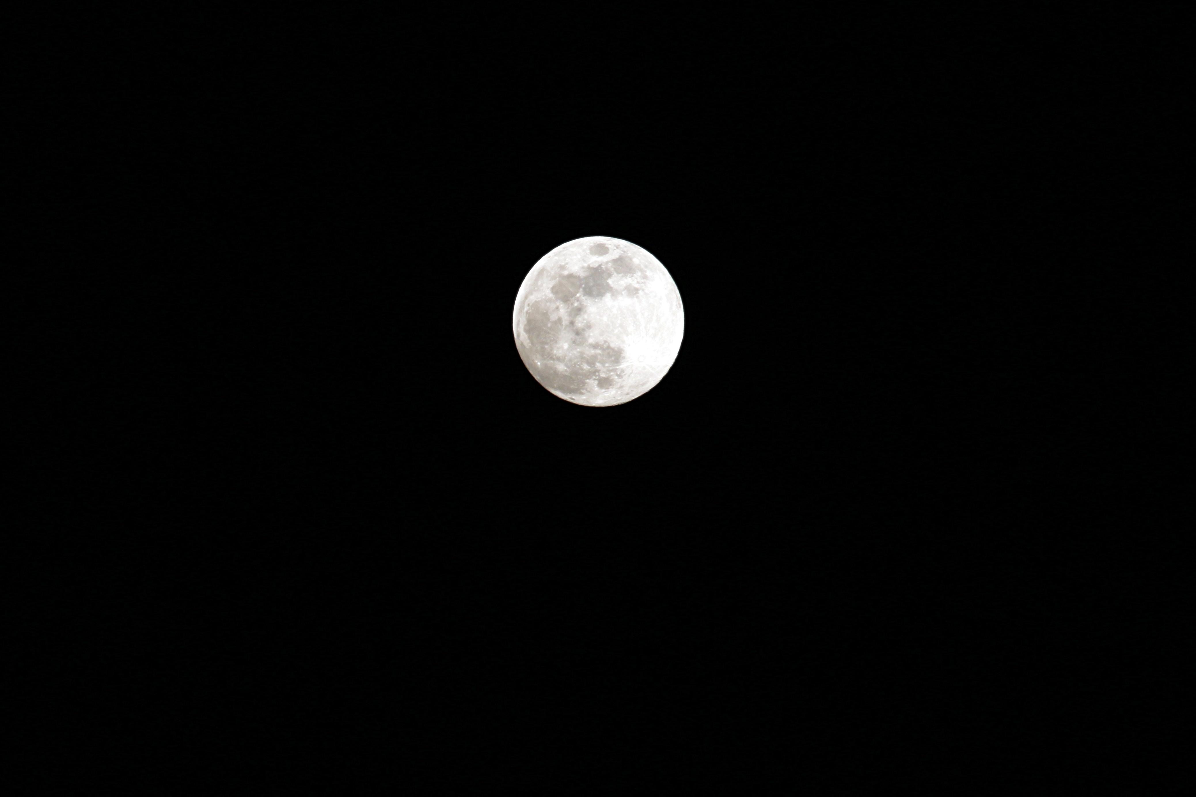 The full moon is seen against the dark night sky