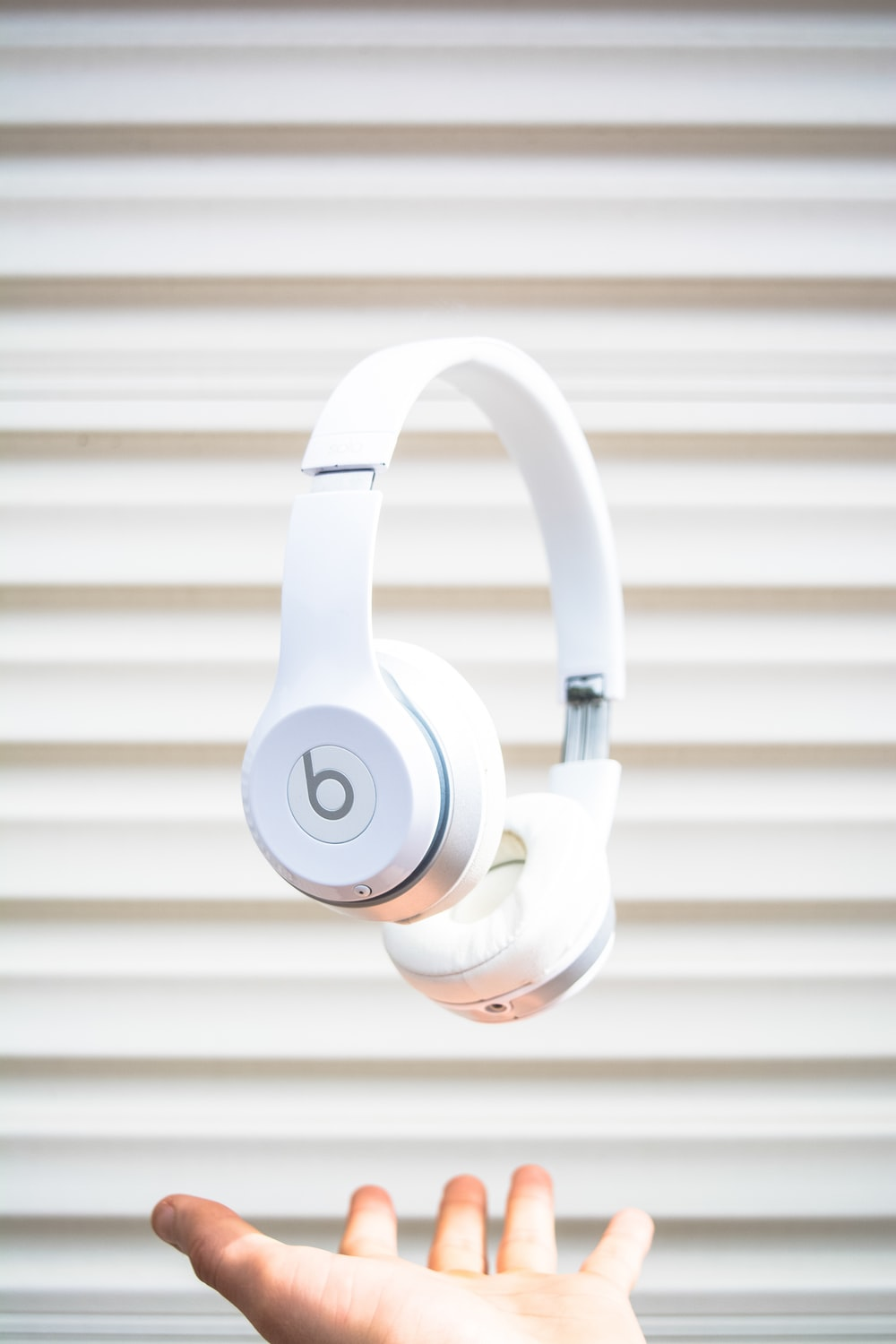 white Beats by Dr. Dre headphones on mid air