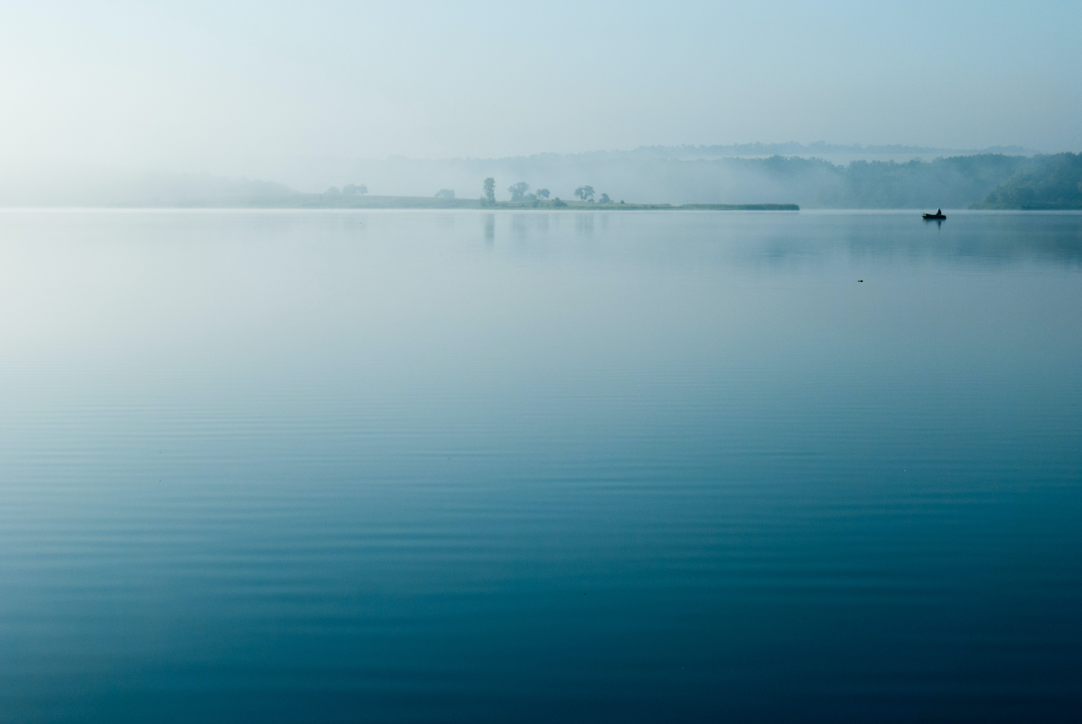 Boats sit in calm blue waters on a misty evening