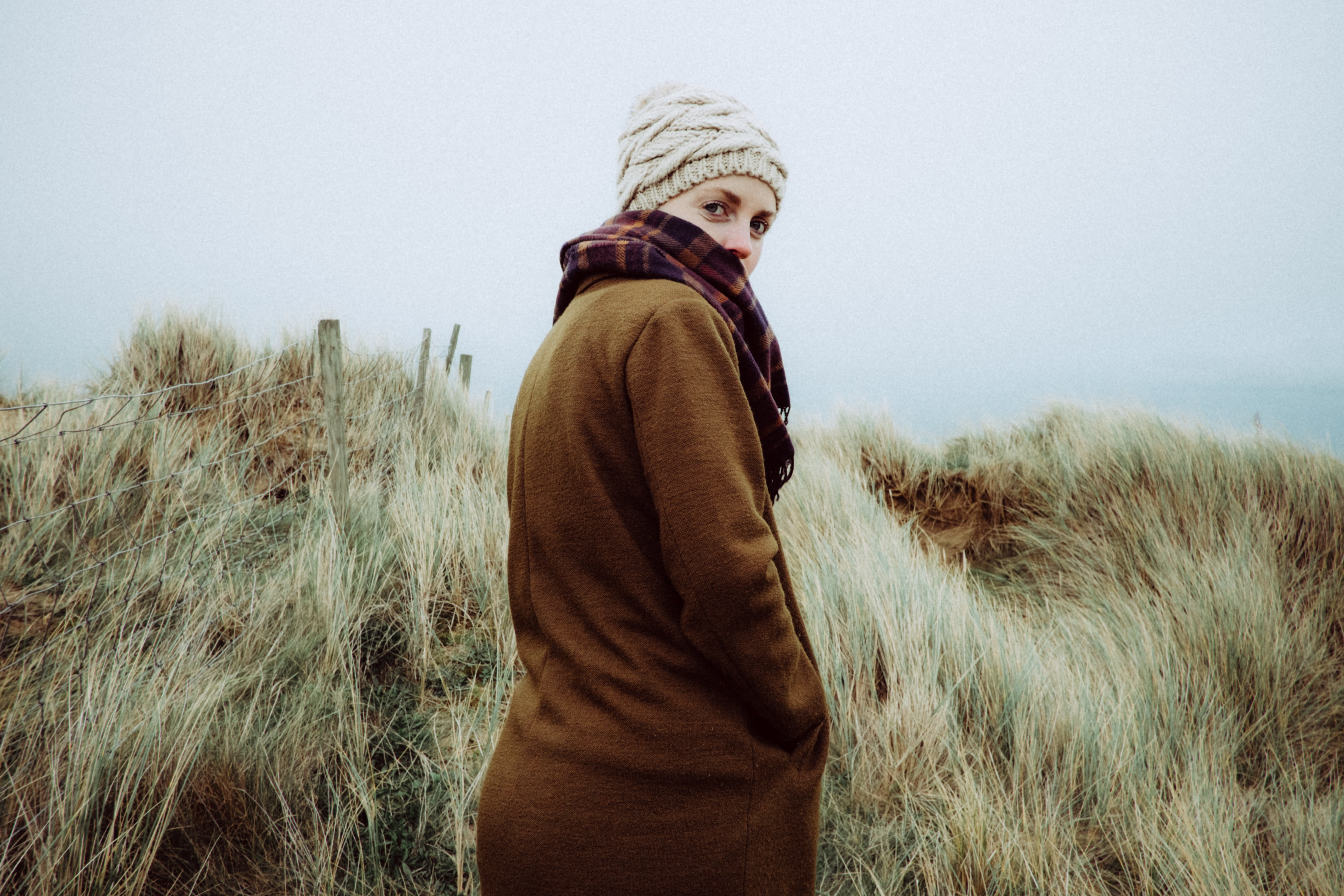 A woman in a knit cap and sweater turns toward the camera among coastal dunes