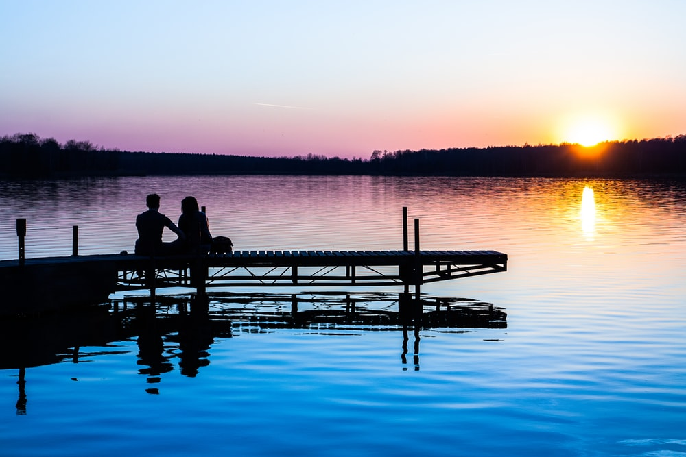 silhouette of two persons sitting on dock