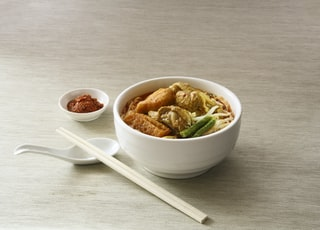 white ceramic bowl filled with cooked noodles near white chopsticks