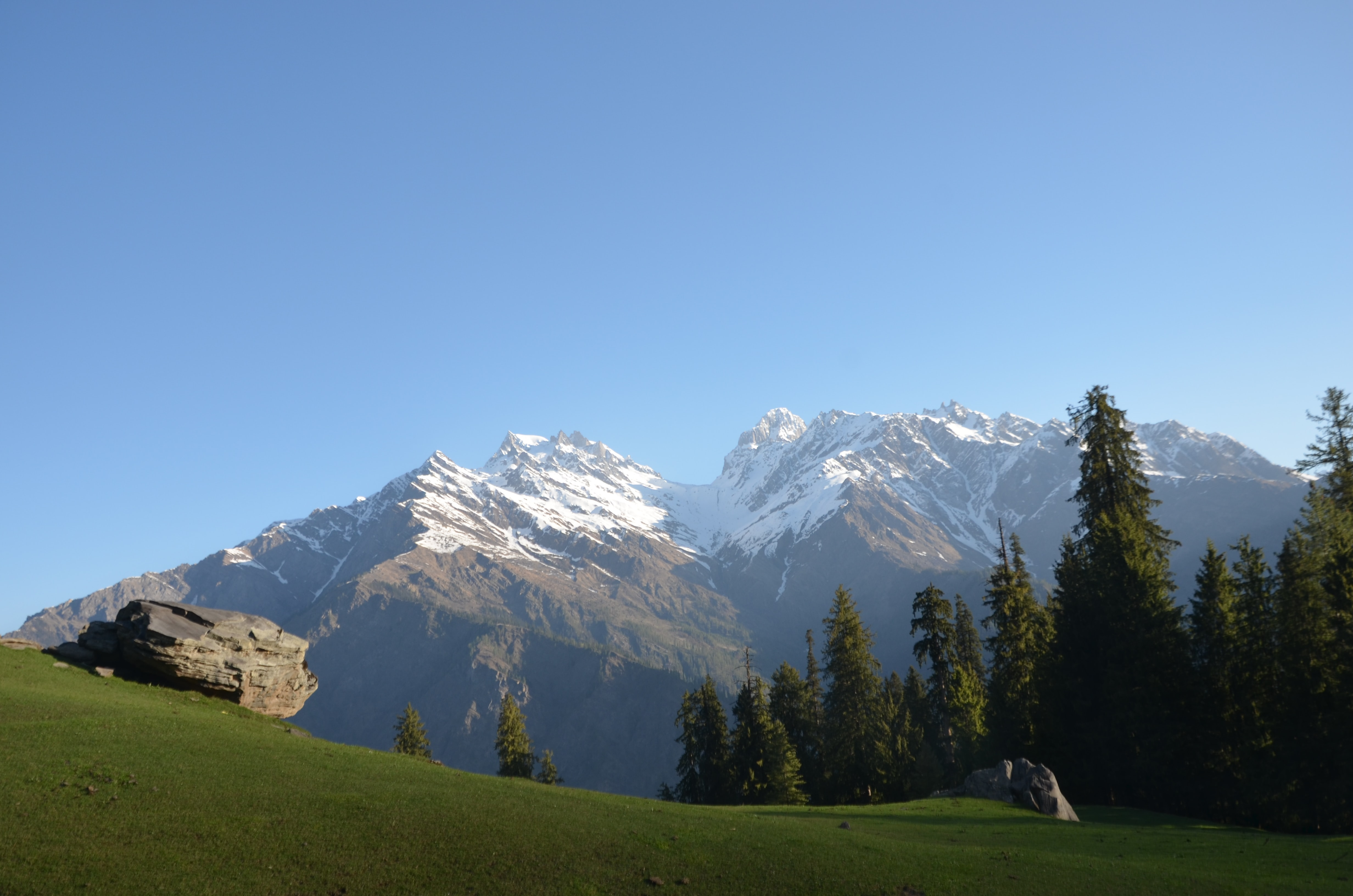 A large boulder in a green meadow at the foot of snowy mountains in Kasol