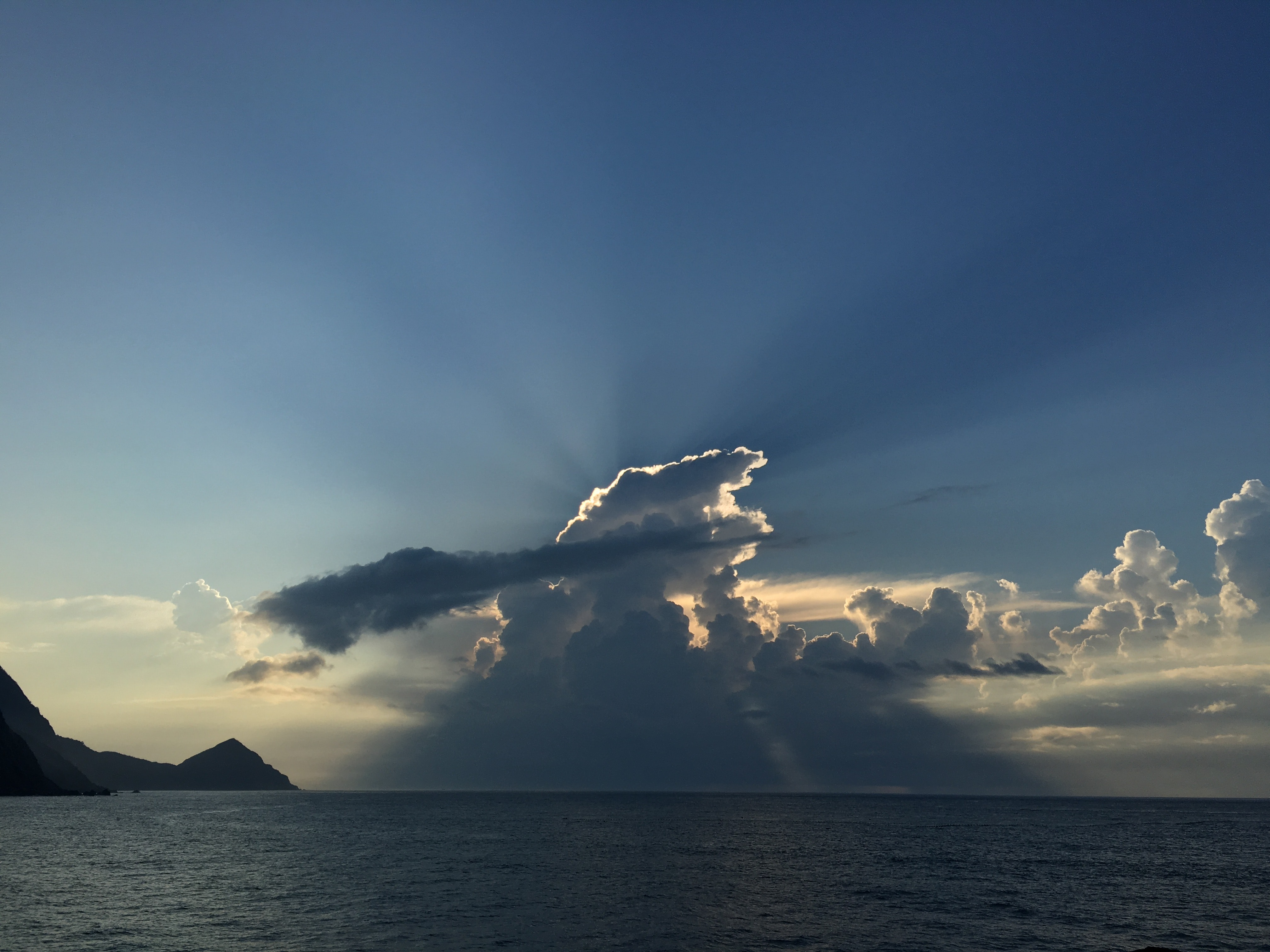 panoramic photo of sea with clouds covering the sun during daytime