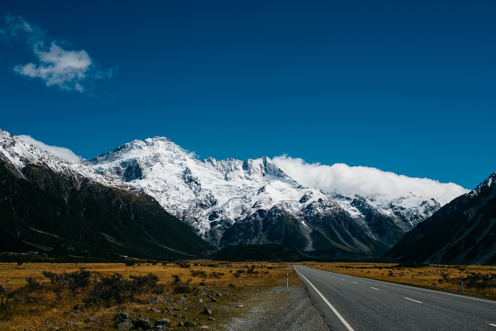 road toward mountain with snow at daytime