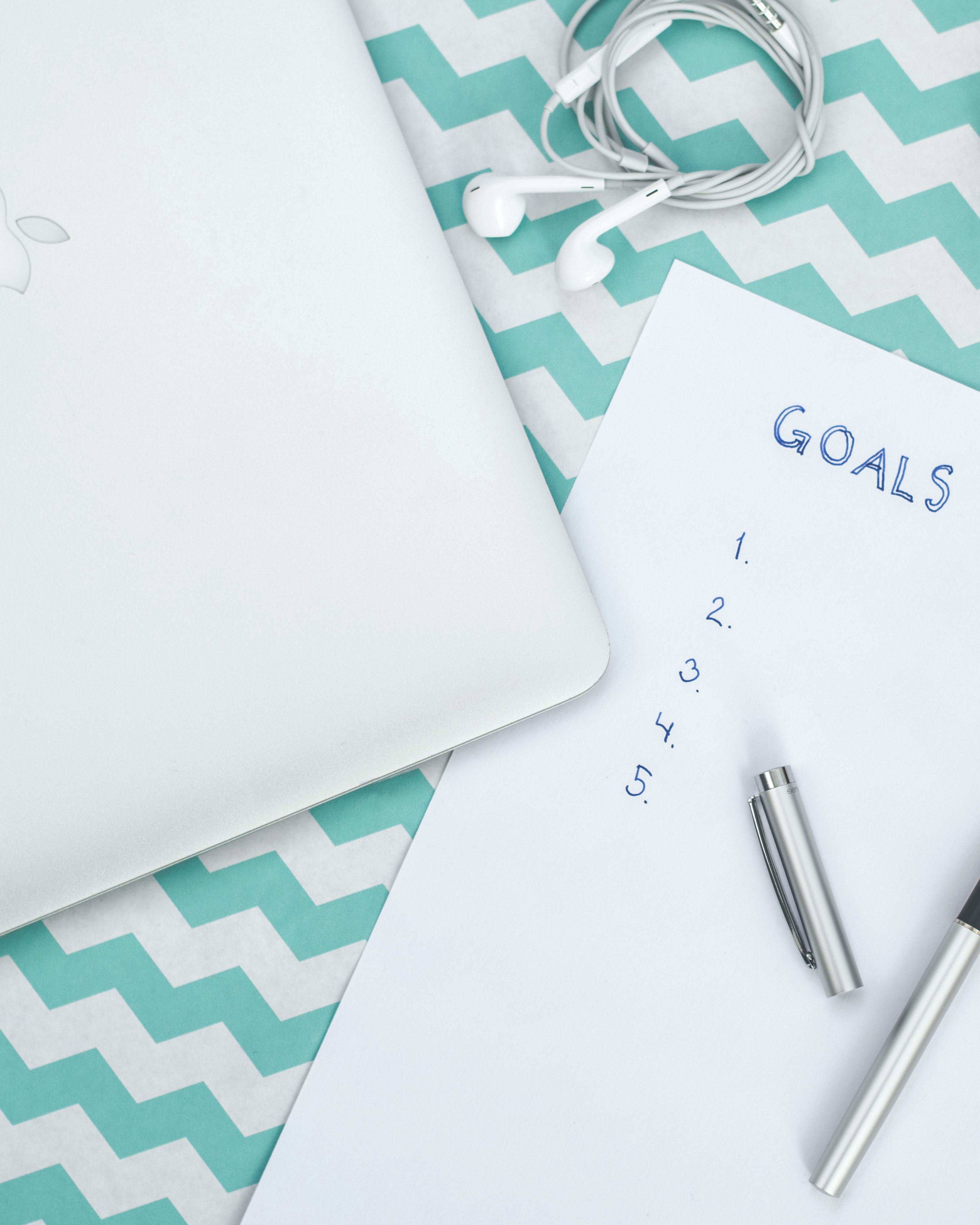 "A pen open on top of a piece of paper, where it says ""Goals,"" and an empty numbered list."