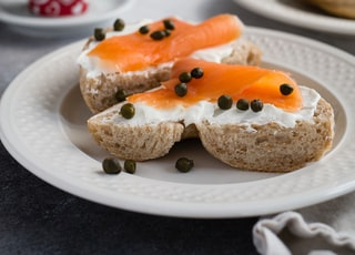 tuna on bread with whip cream and pepper on round plate on top of table