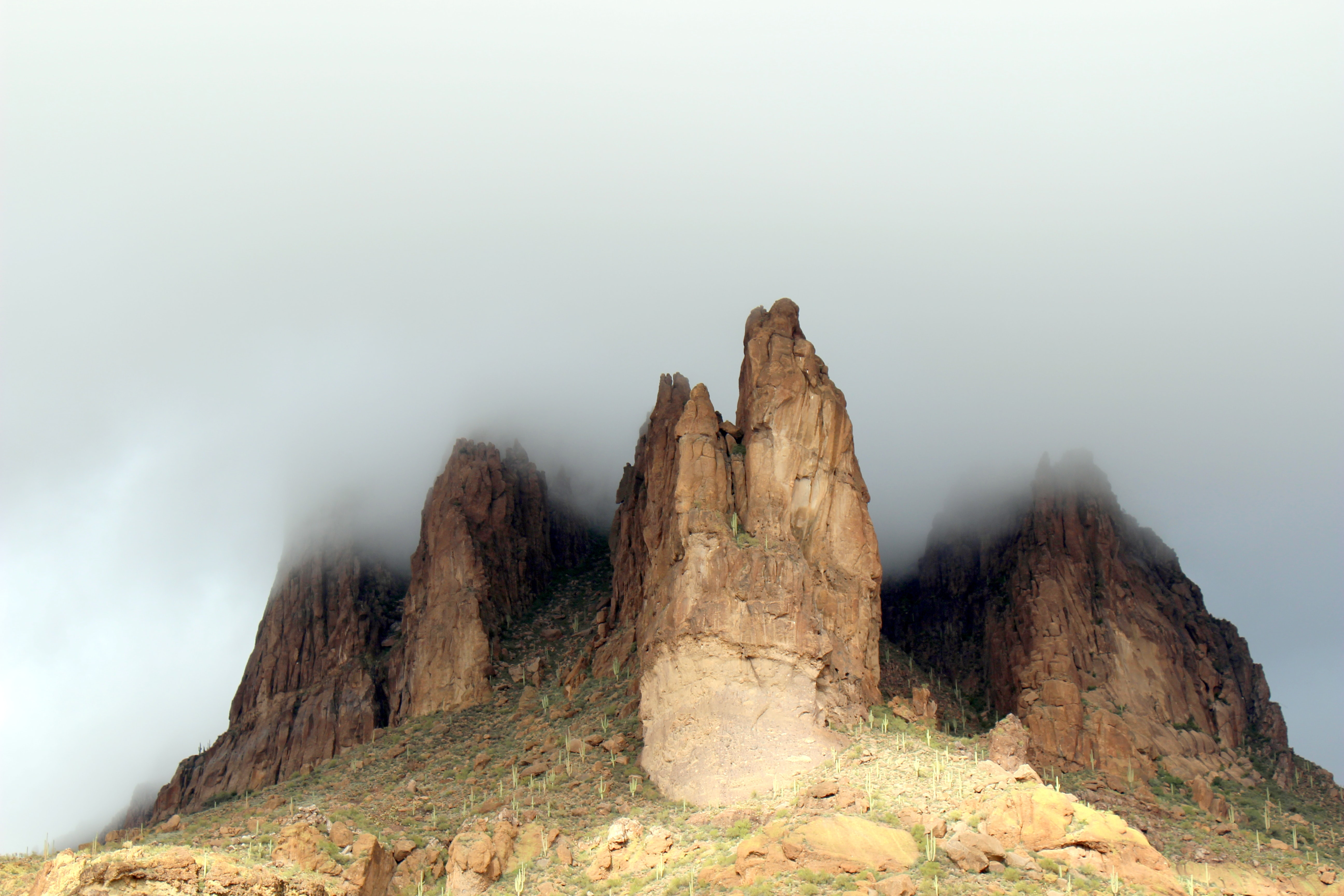Fog covers the rocky peaks of the mountainside in Gold Canyon