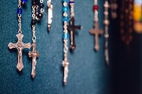 Cross pendants on gem necklaces hanging down a wall.