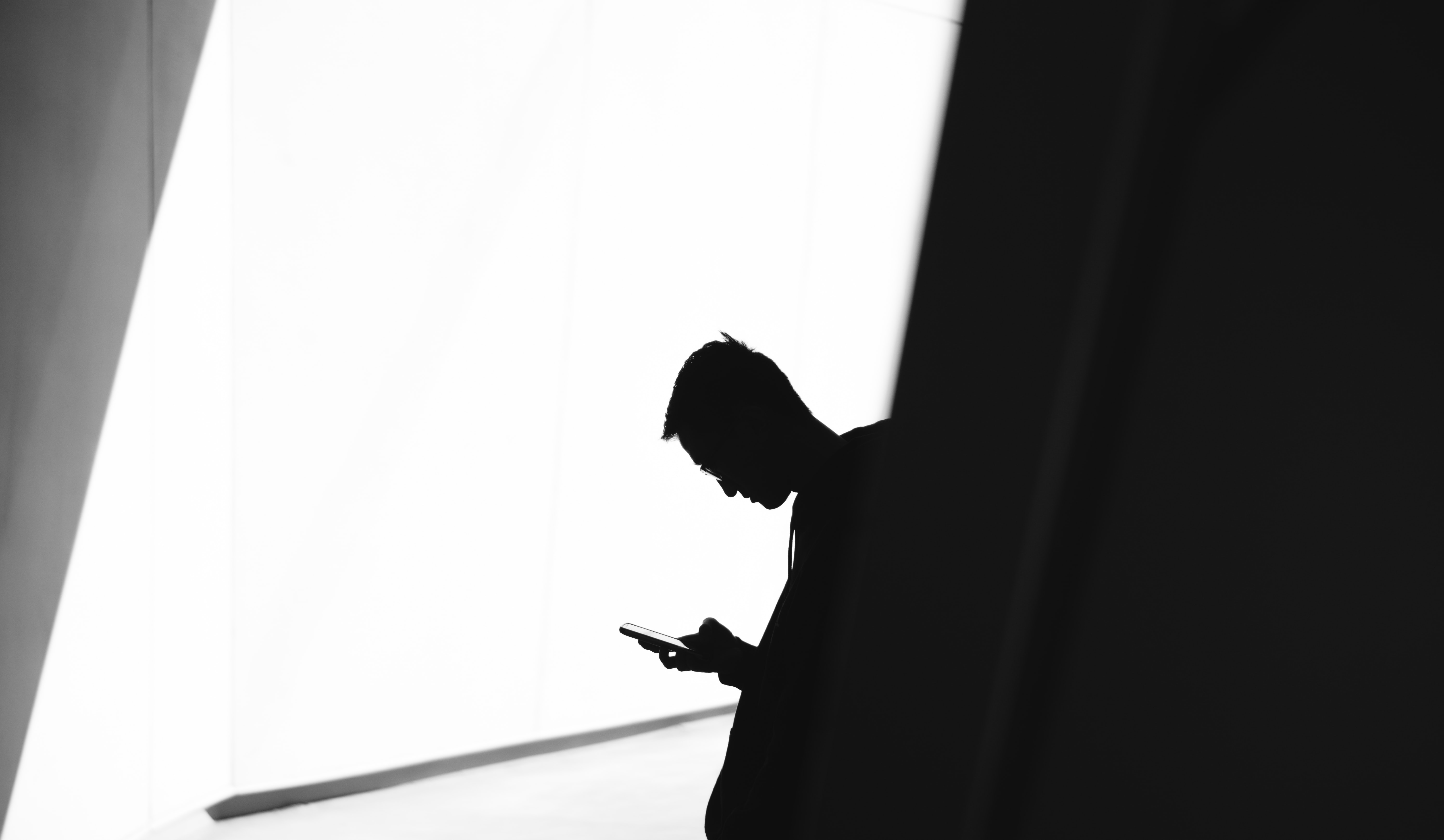 Silhouette of a man looking at his phone against a bright wall in Toronto.