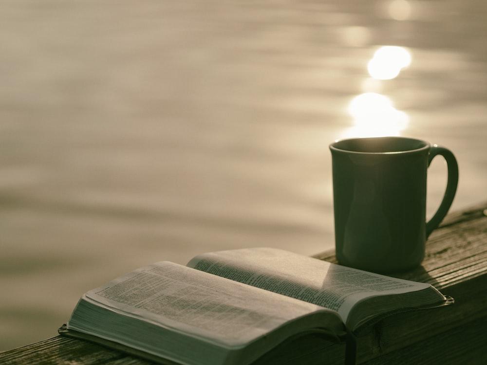 green ceramic mug beside book