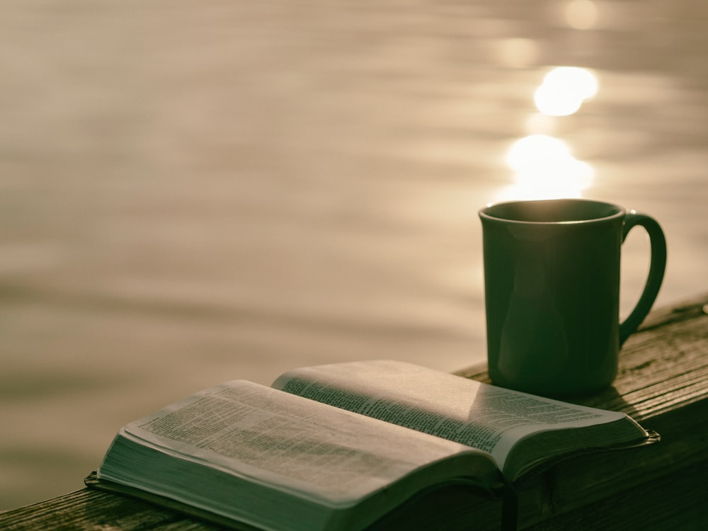green ceramic mug beside book