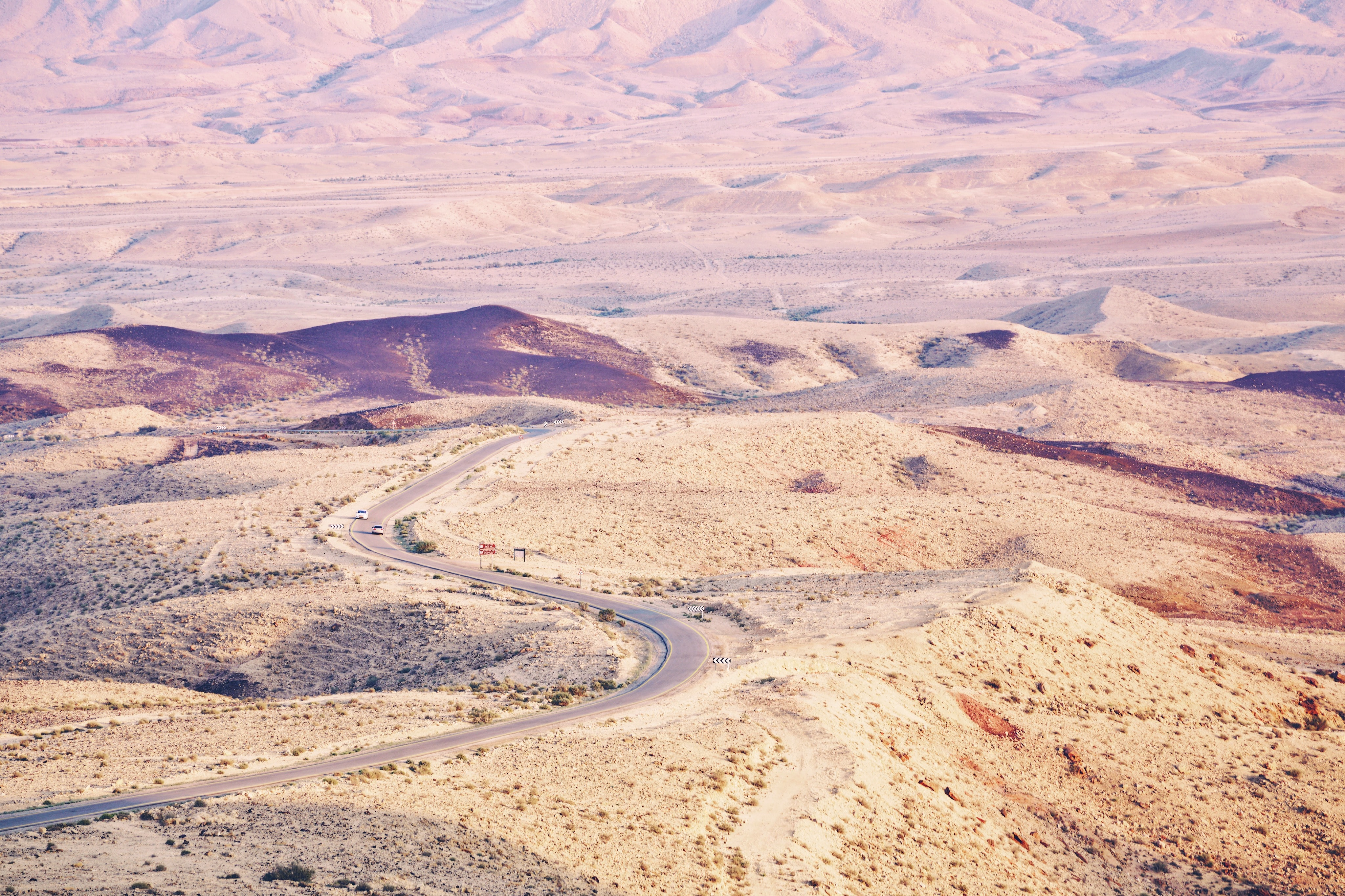 aerial photography of road between desert at daytime