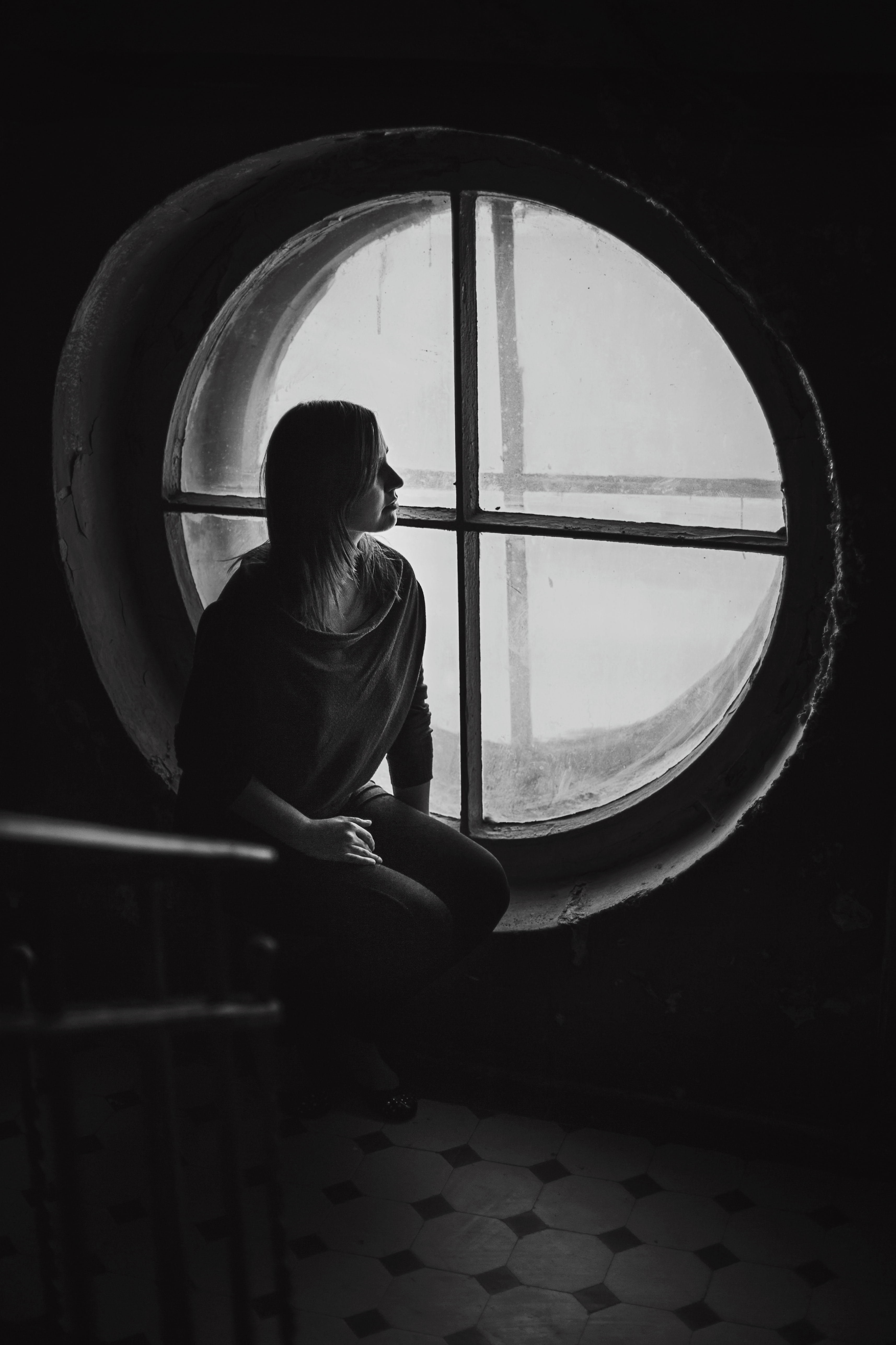grayscale photo of woman sits near round wooden framed window