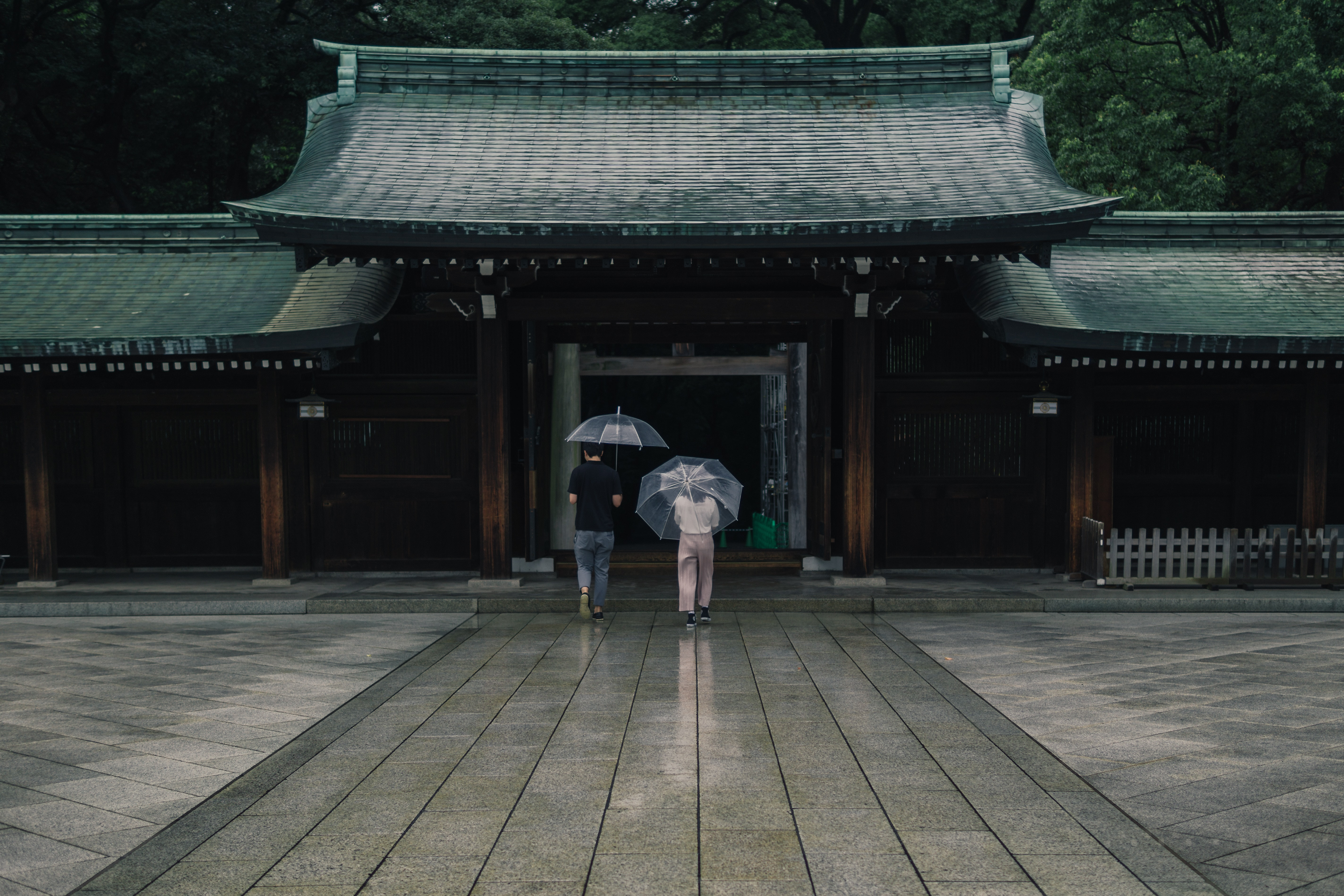 two people holding umbrellas near brown building during rainy season