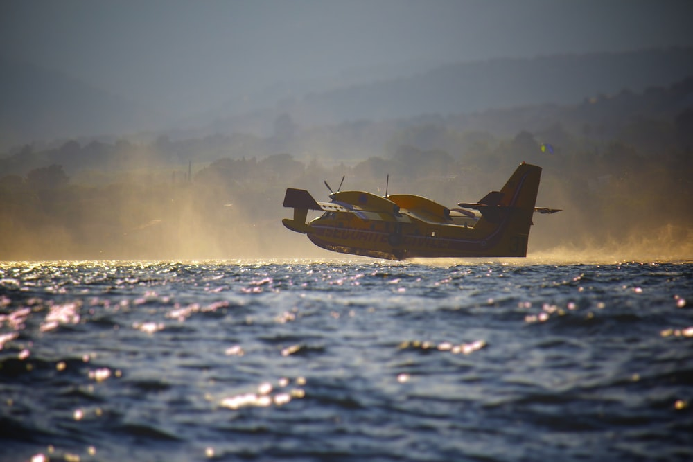 low angle photography of amphibian plane flying at low altitude near water at daytime