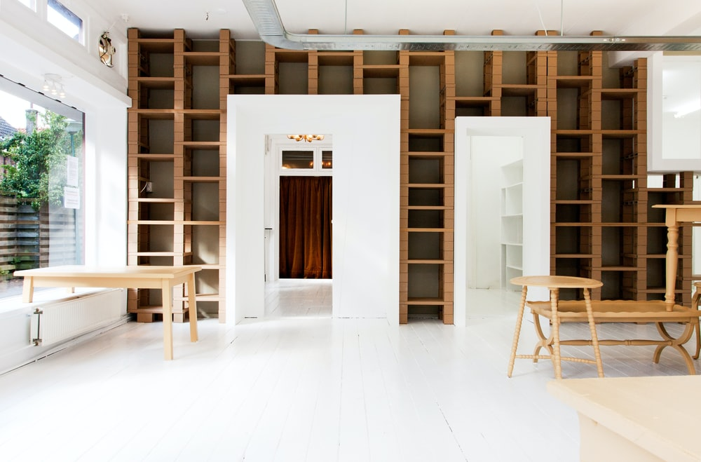 two beige wooden tables in white room