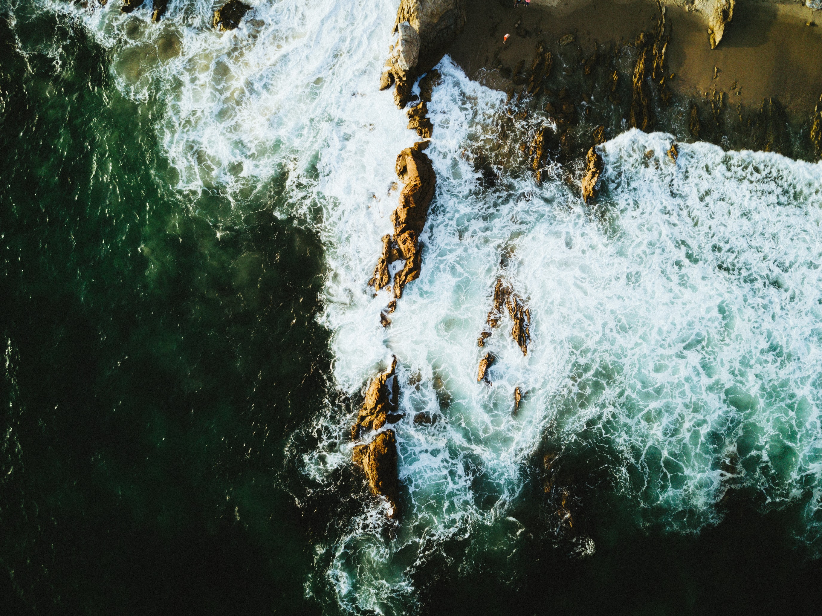 Drone view of the ocean washing on the cliffs at Corona Del Mar