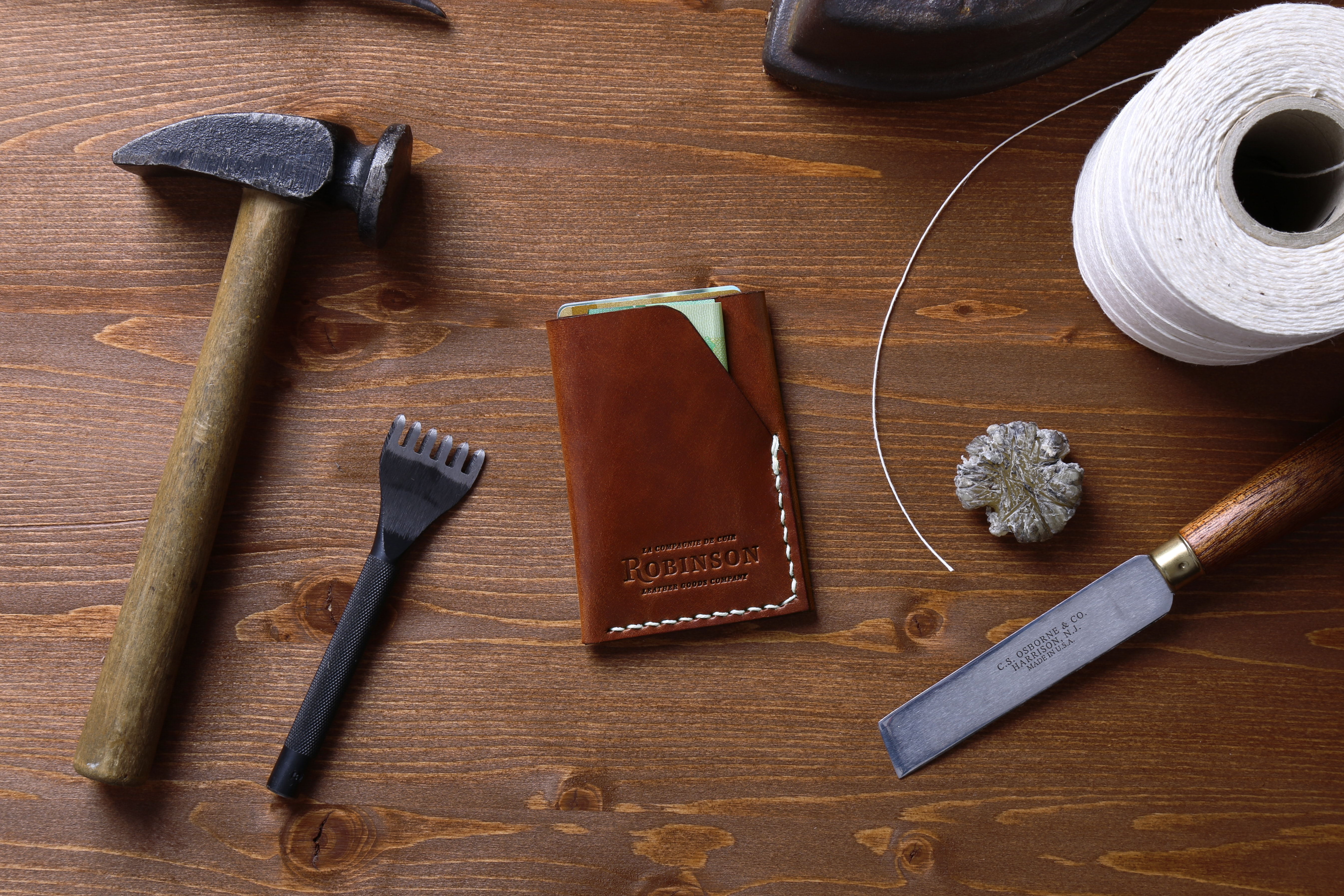 An overhead shot of a leather document sleeve among various tools on a wooden surface