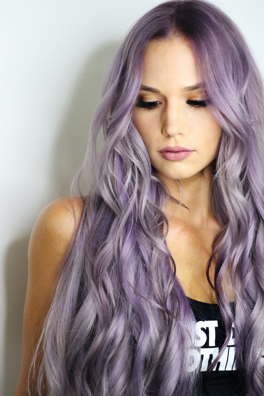 purple haired woman in black top leaning on wall
