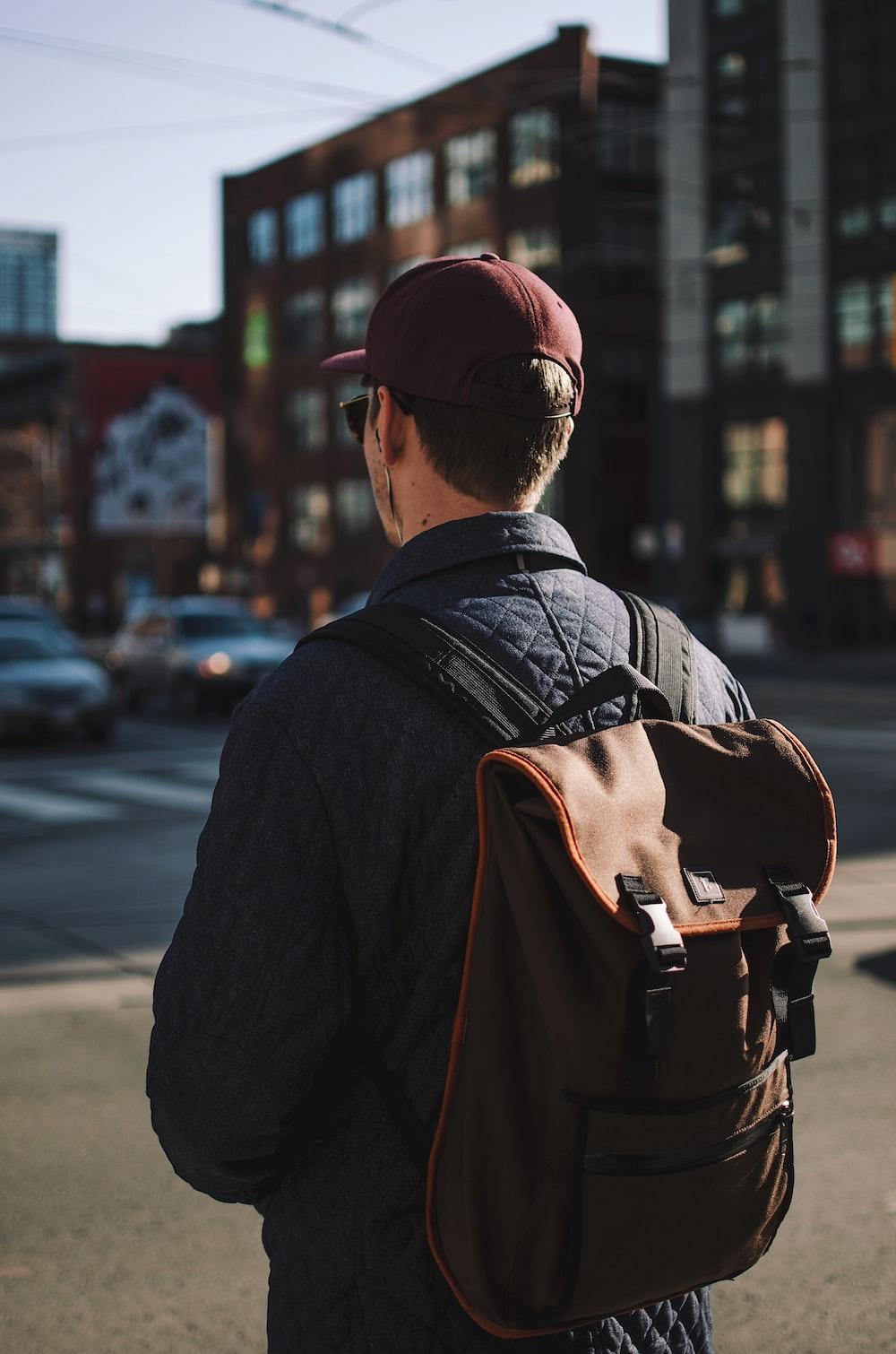 man wearing black jacket and cap standing near road looking forward