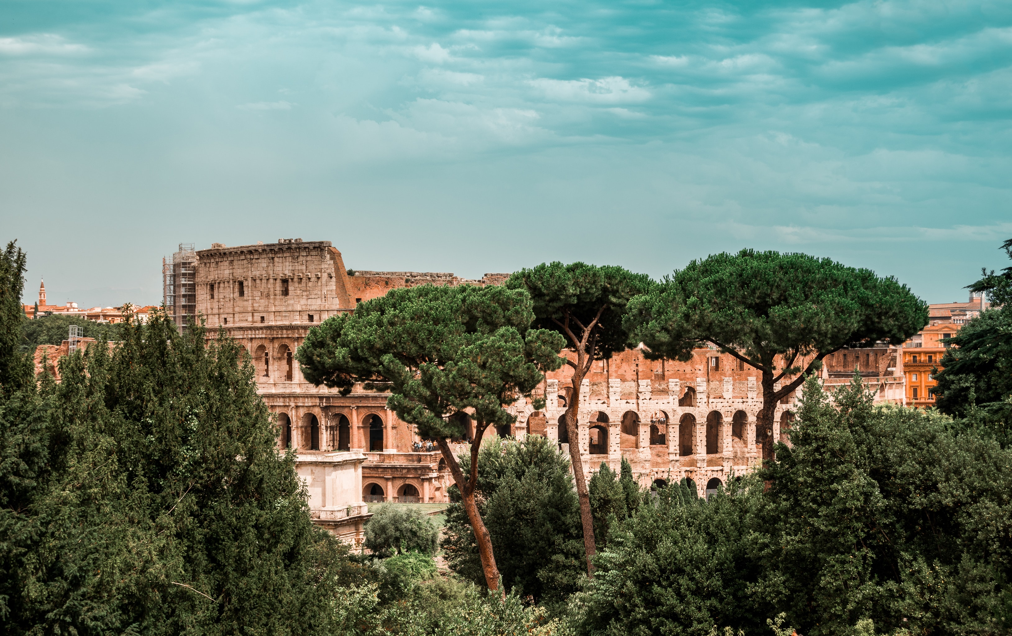 The ruins of the Roman Colosseum behind green trees