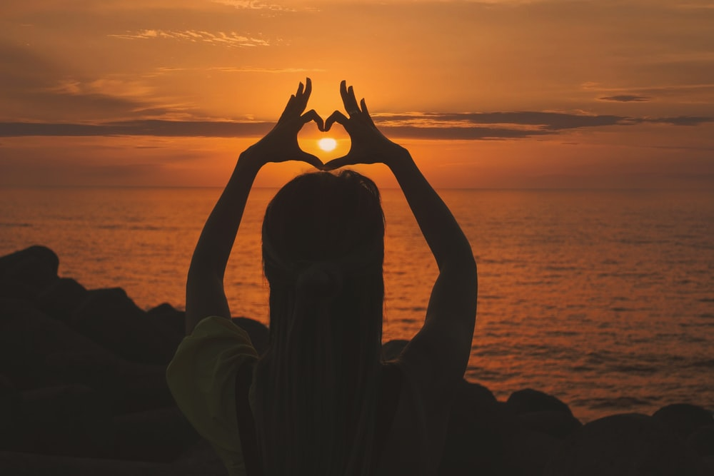 silhouette of woman doing heart sign during sunset