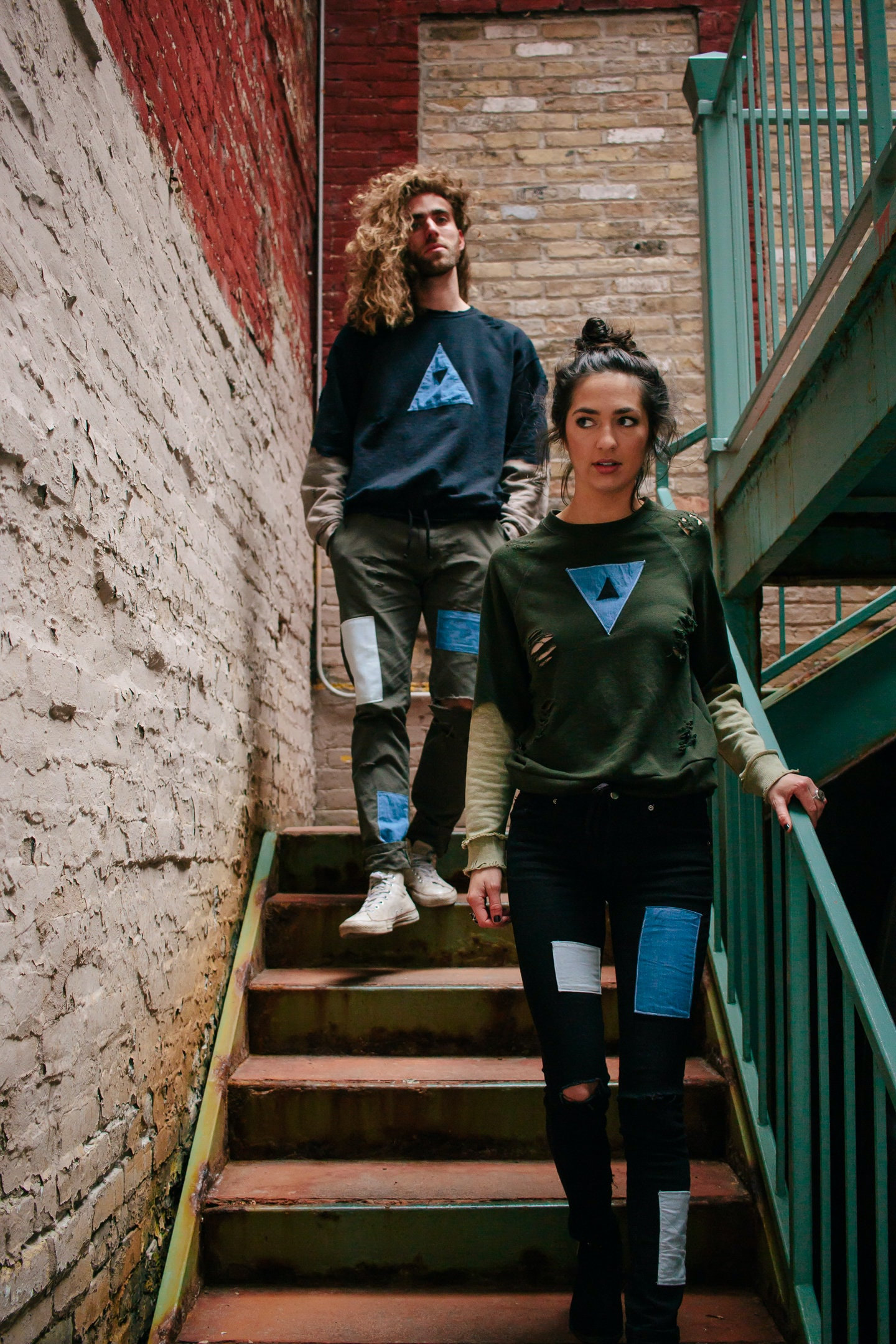 A young woman and a young man walking down the stairs in an old brick stairwell