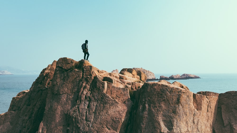 man stands on top of mountain