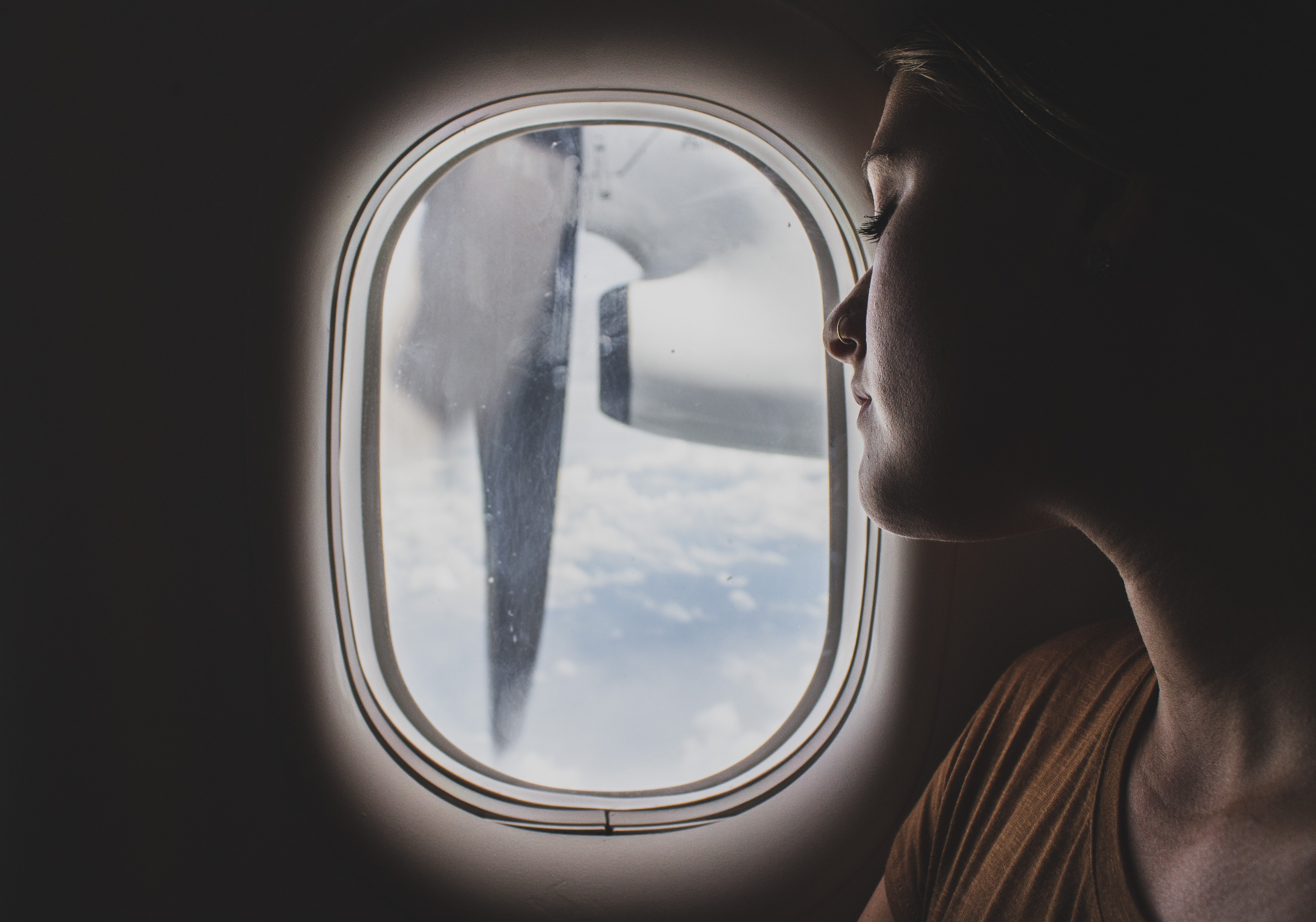 A close-up of a woman's face looking out the oval window on an airplane