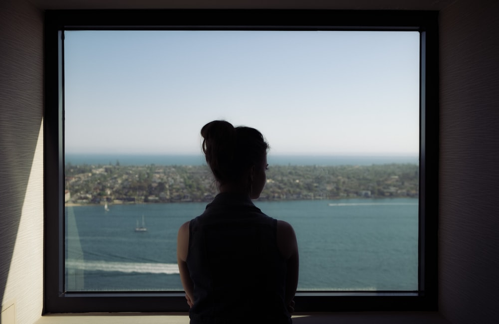 woman wearing off-shoulder shirt standing beside window