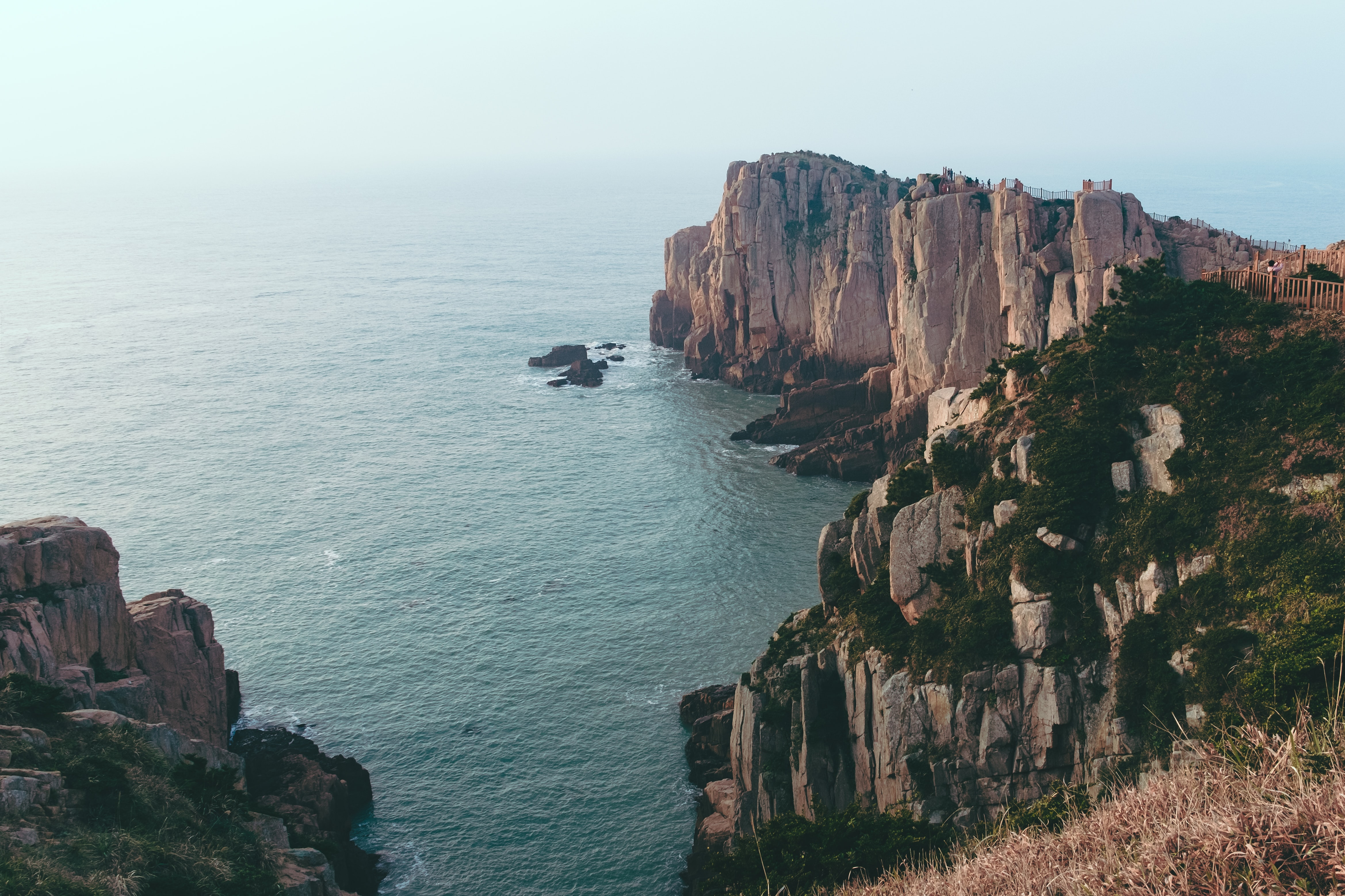 gray and green rock formation near sea during daytime