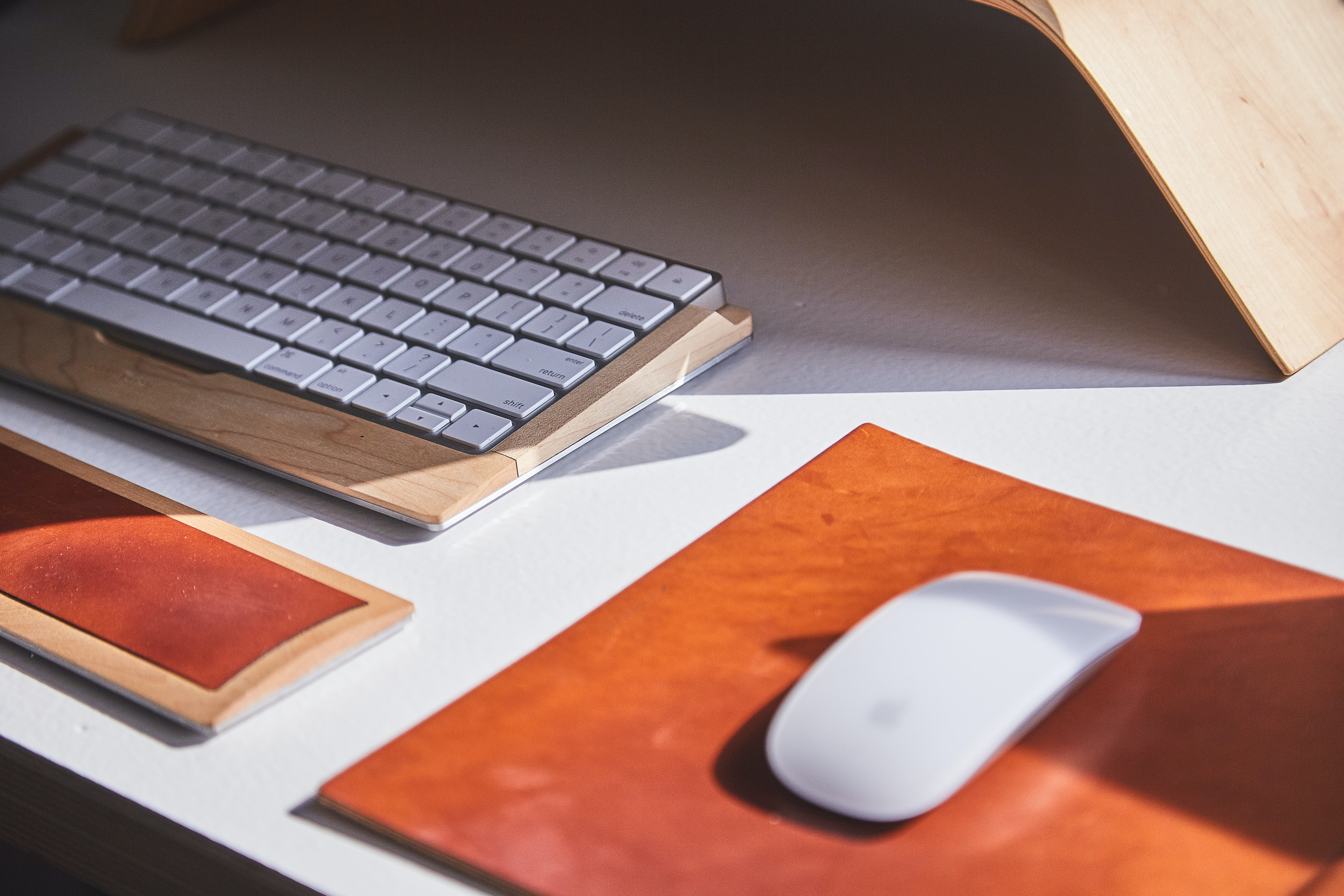 An Apple mouse and keyboard in a wooden casing on a desk