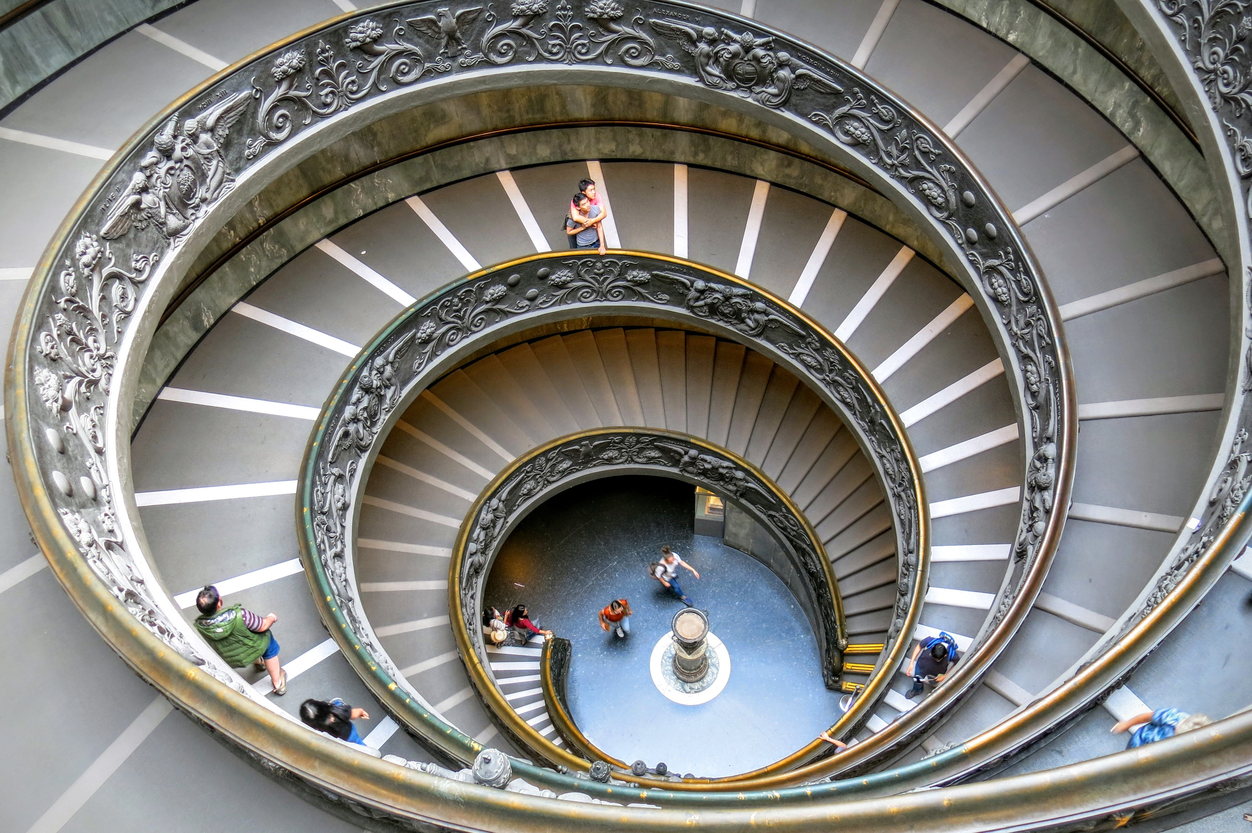Looking down a massive spiral staircase while people climb up in the Vatican Museums