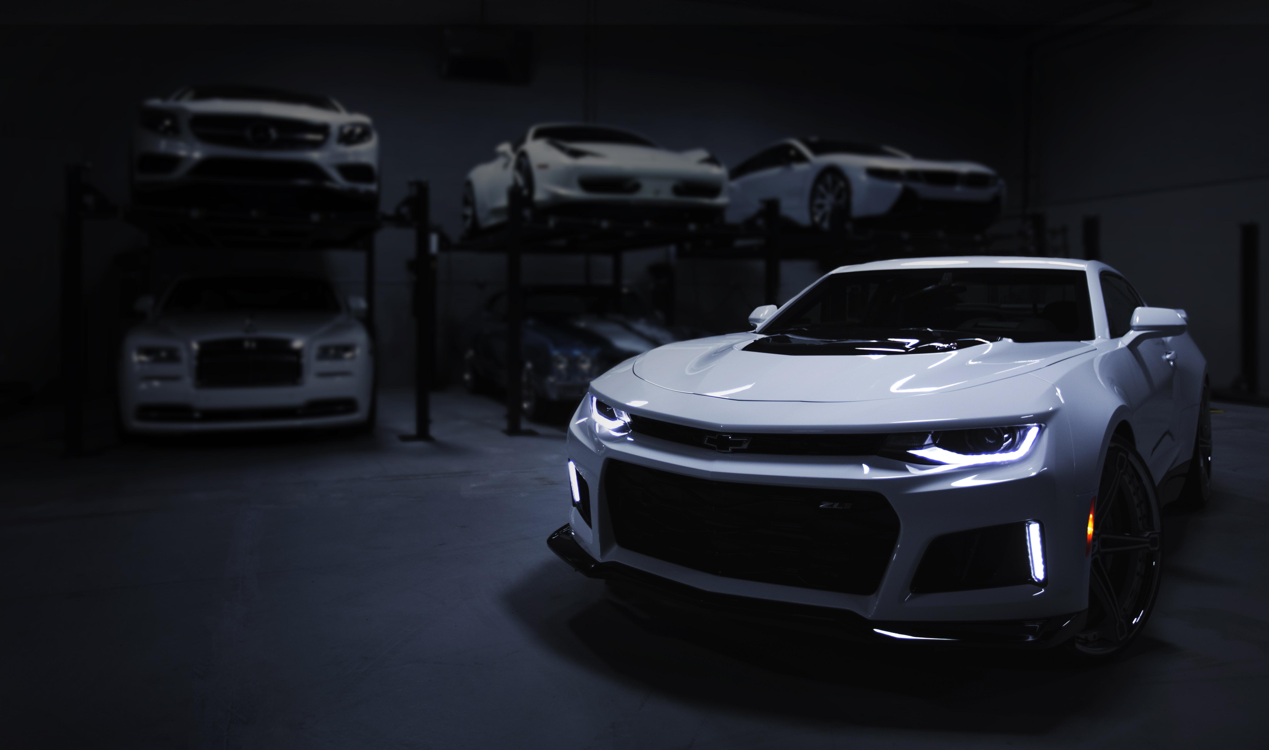 White sports car inside a dark parking garage.