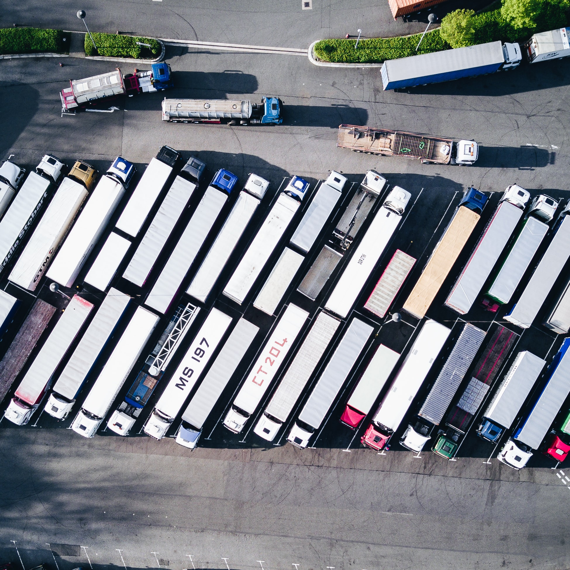 A drone shot of two rows of parked trucks with long trailers