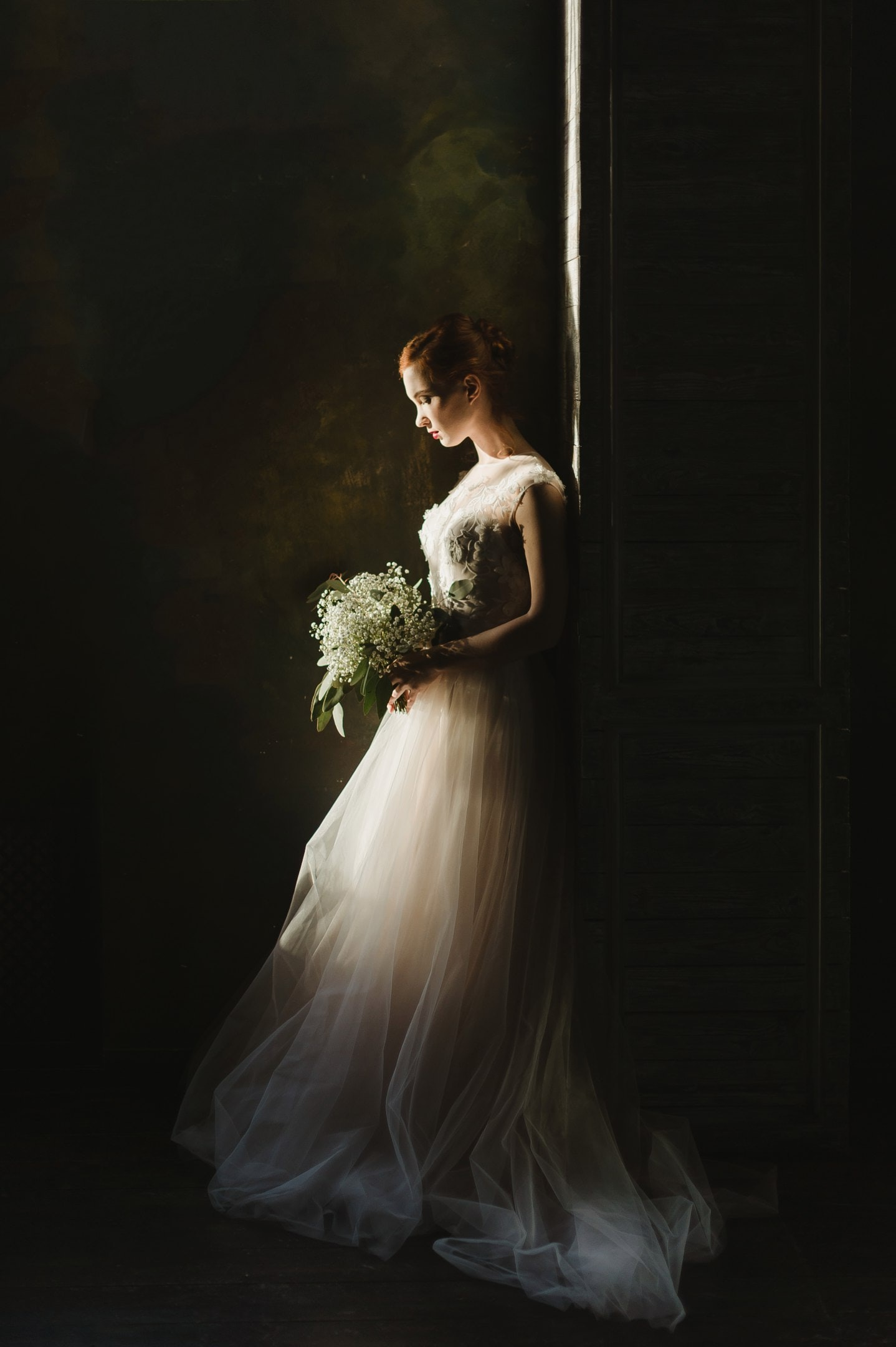 Bride in a wedding gown with a floral bouquet stands in the shadows