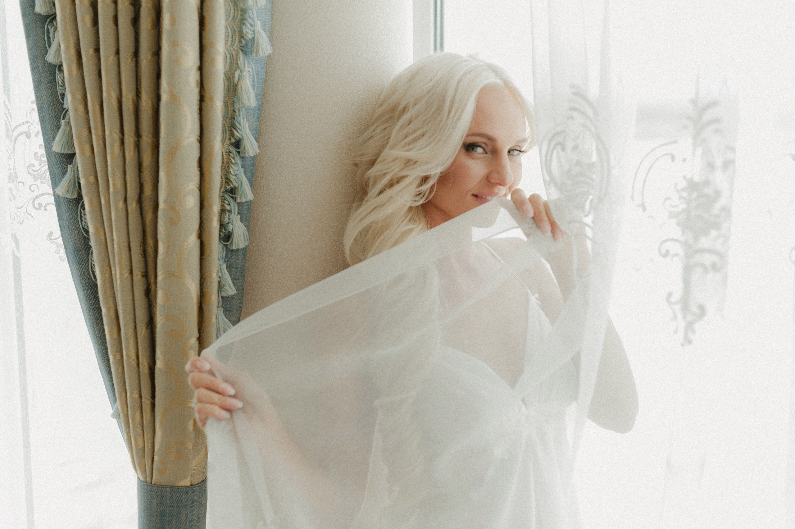 A smiling blonde woman in white gauzy lingerie poses by a window and curtain