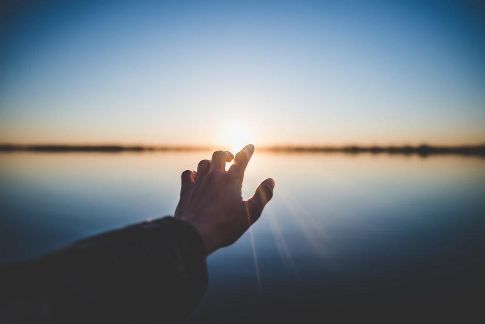 landscape photography of person's hand in front of sun