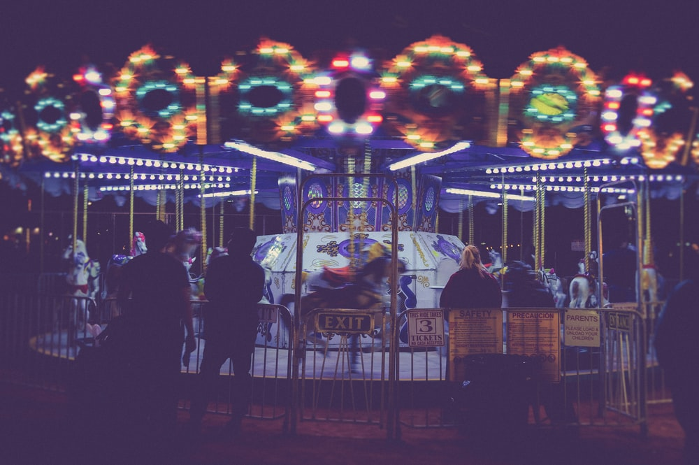 people standing besides Merry-Go-Round during nighttime